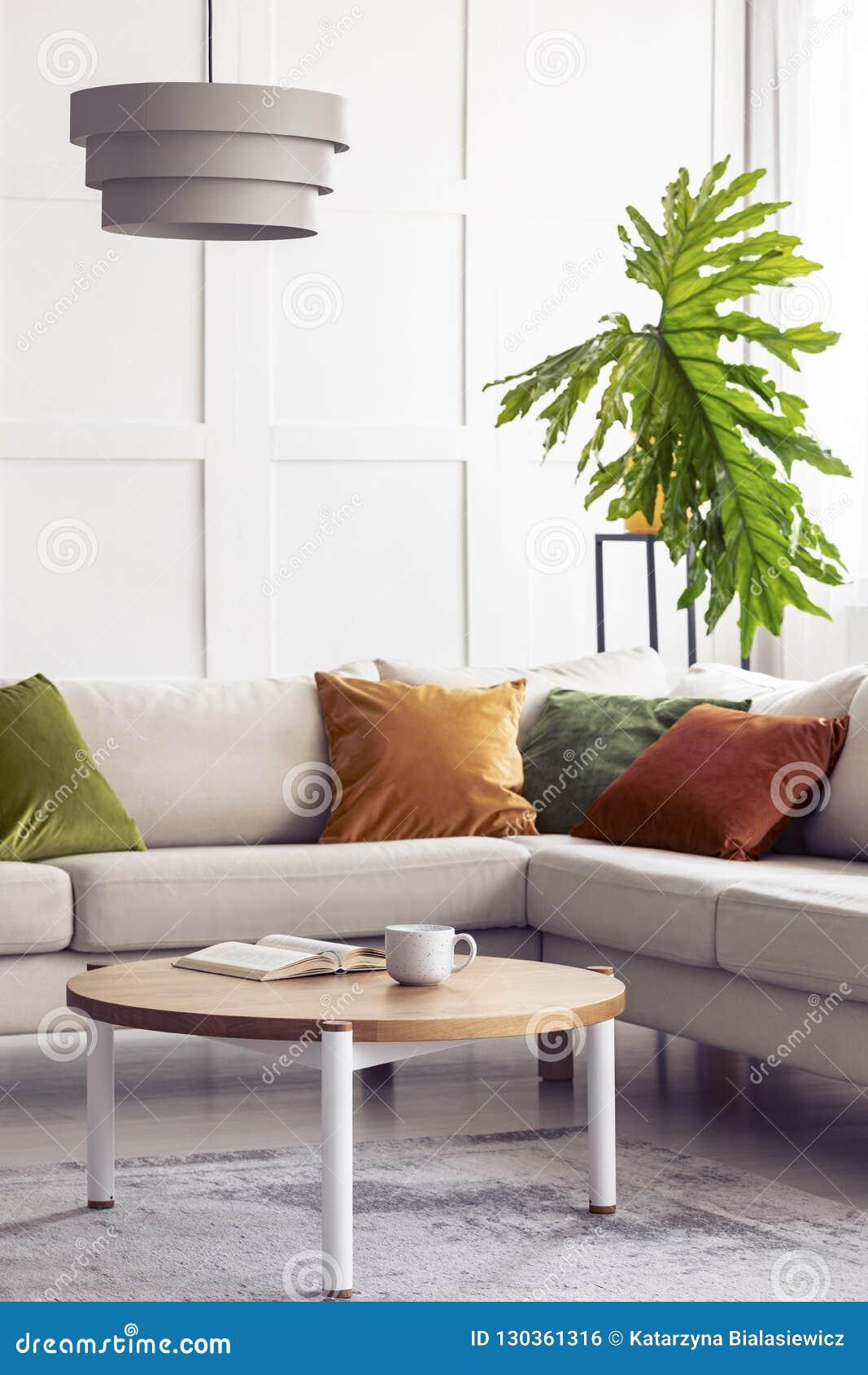 Folha verde grande e lâmpada branca simples acima do sofá de canto no interior colorido da sala de visitas, foto real