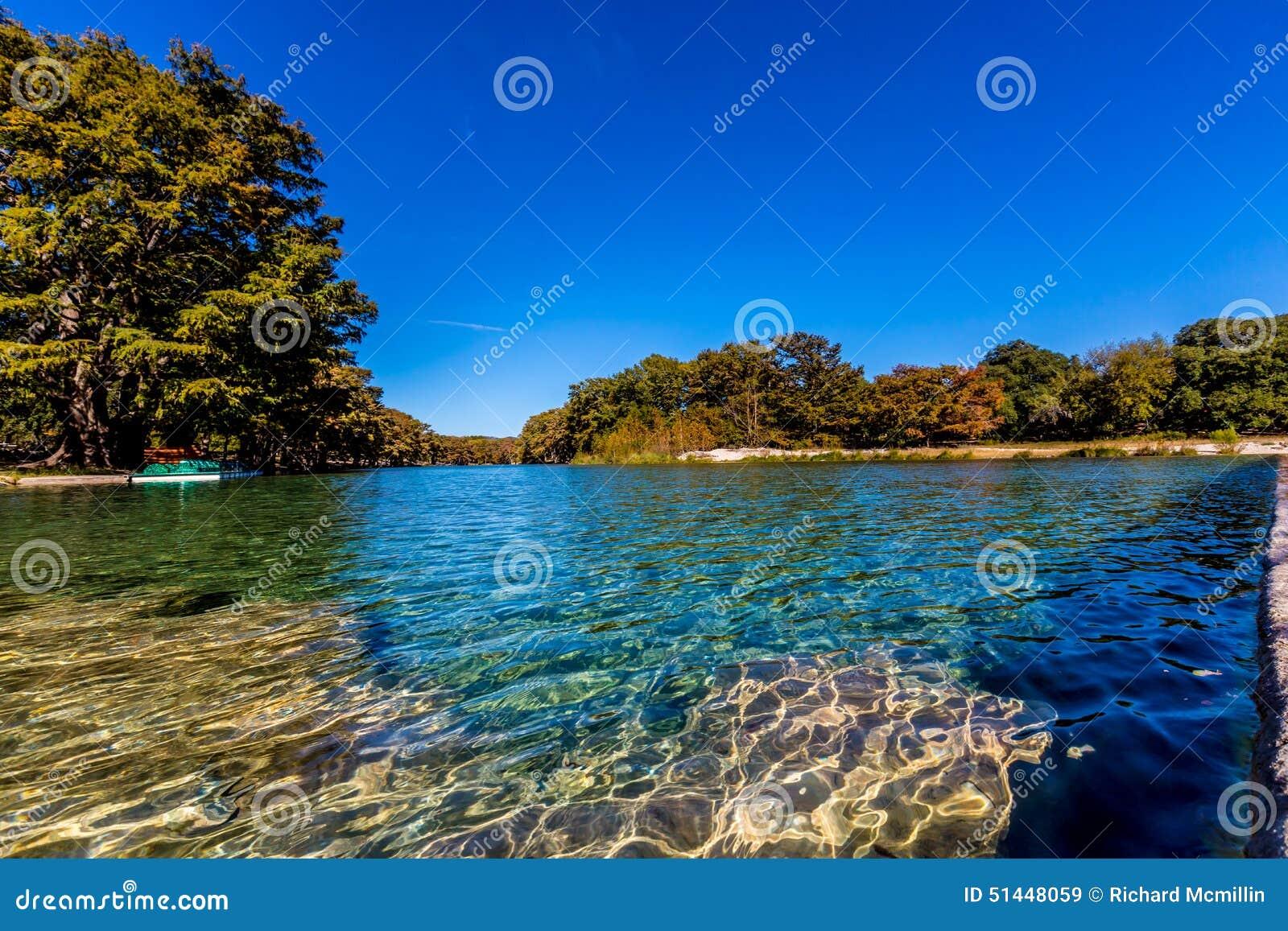 Folhagem de outono bonita brilhante em Crystal Clear Frio River