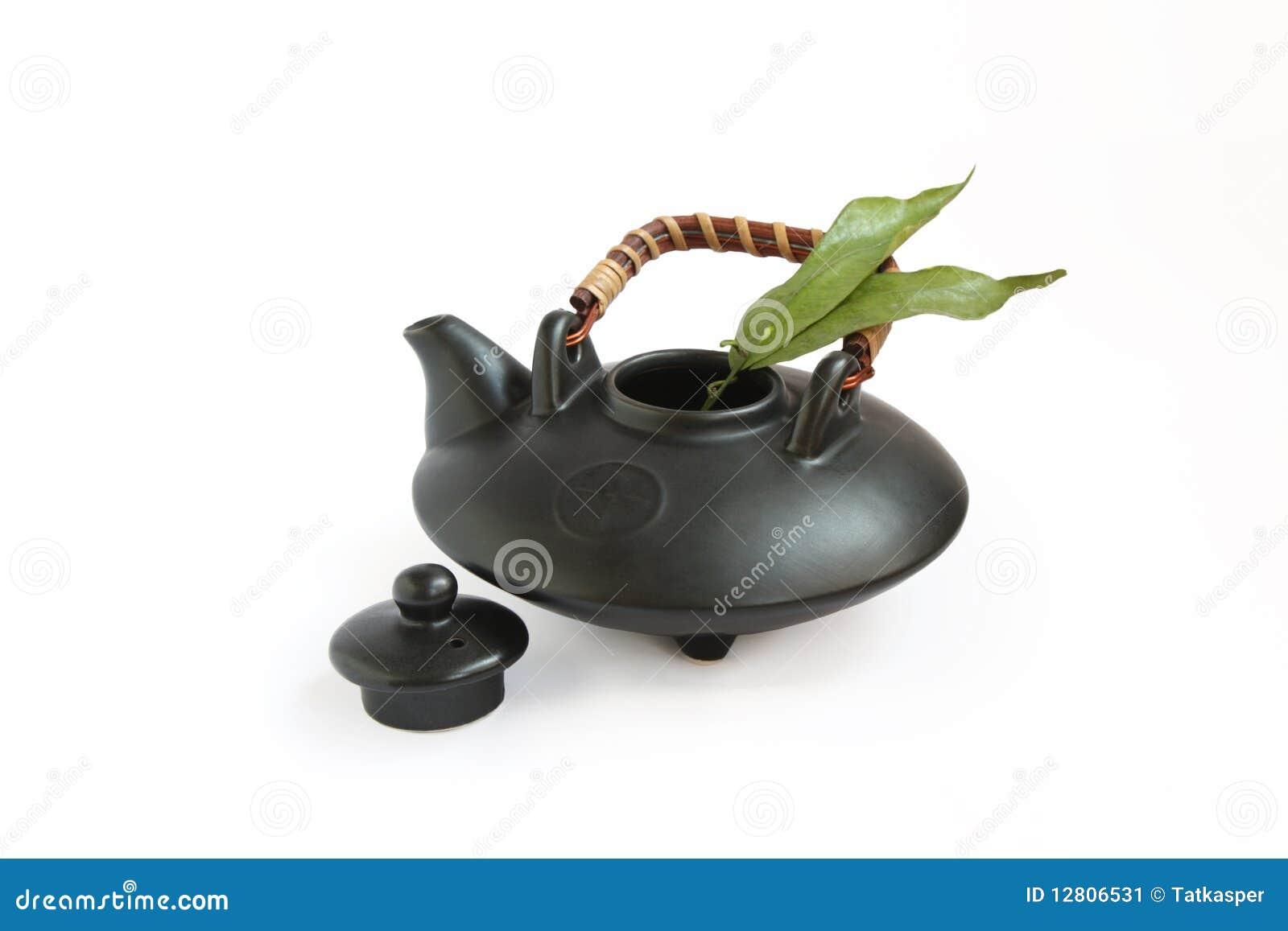 Folhas orientais pretas do teapot e do chá