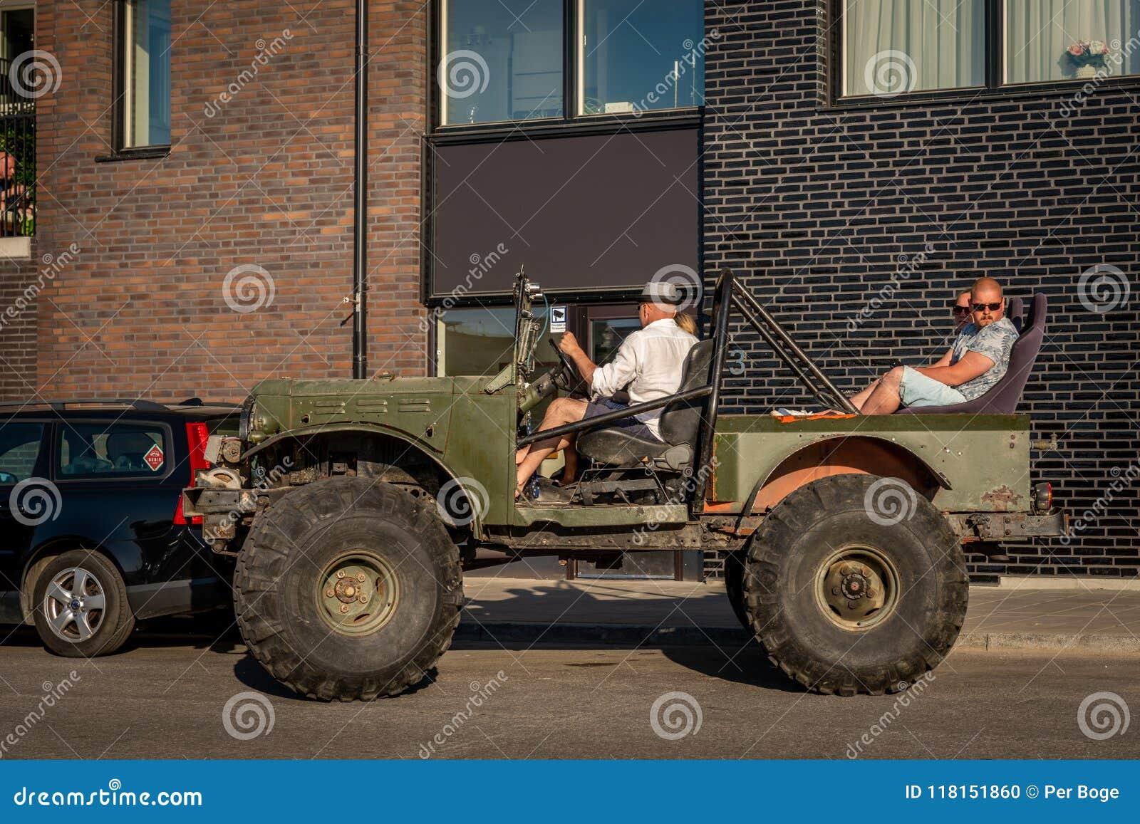 Folk i en öppen offroad bil med jätte- gummihjul