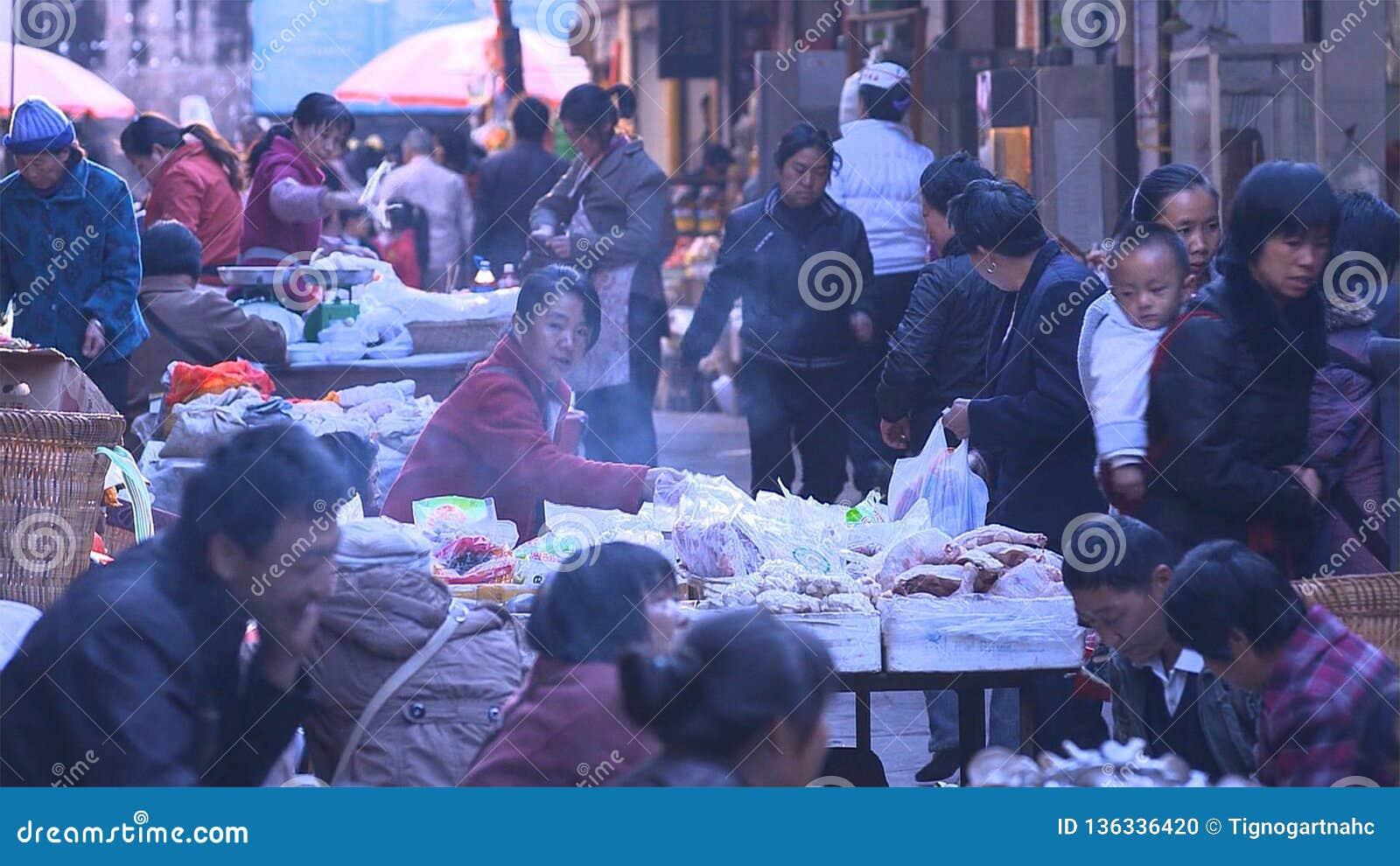 Folk i kinesisk marknadsbygd som köper eller säljer något yunnan Kina