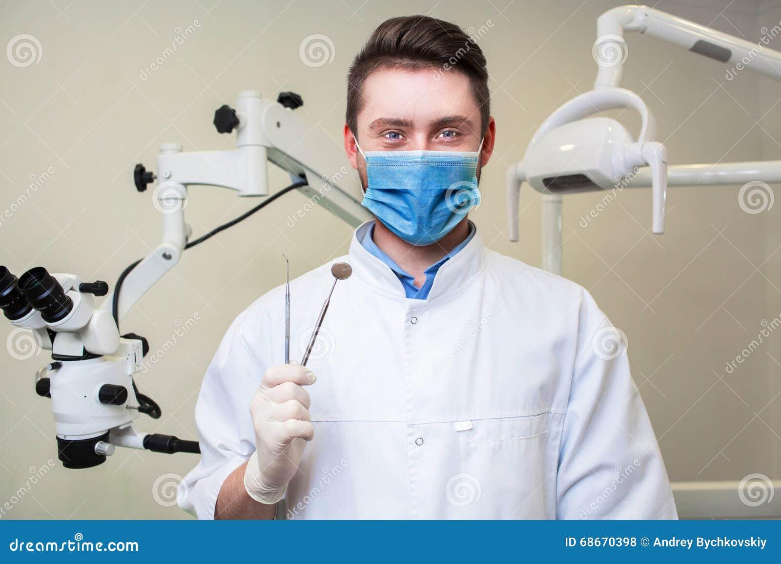 Folk-, medicin-, stomatology- och sjukvårdbegrepp - lycklig ung manlig tandläkare med hjälpmedel över medicinsk kontorsbakgrund