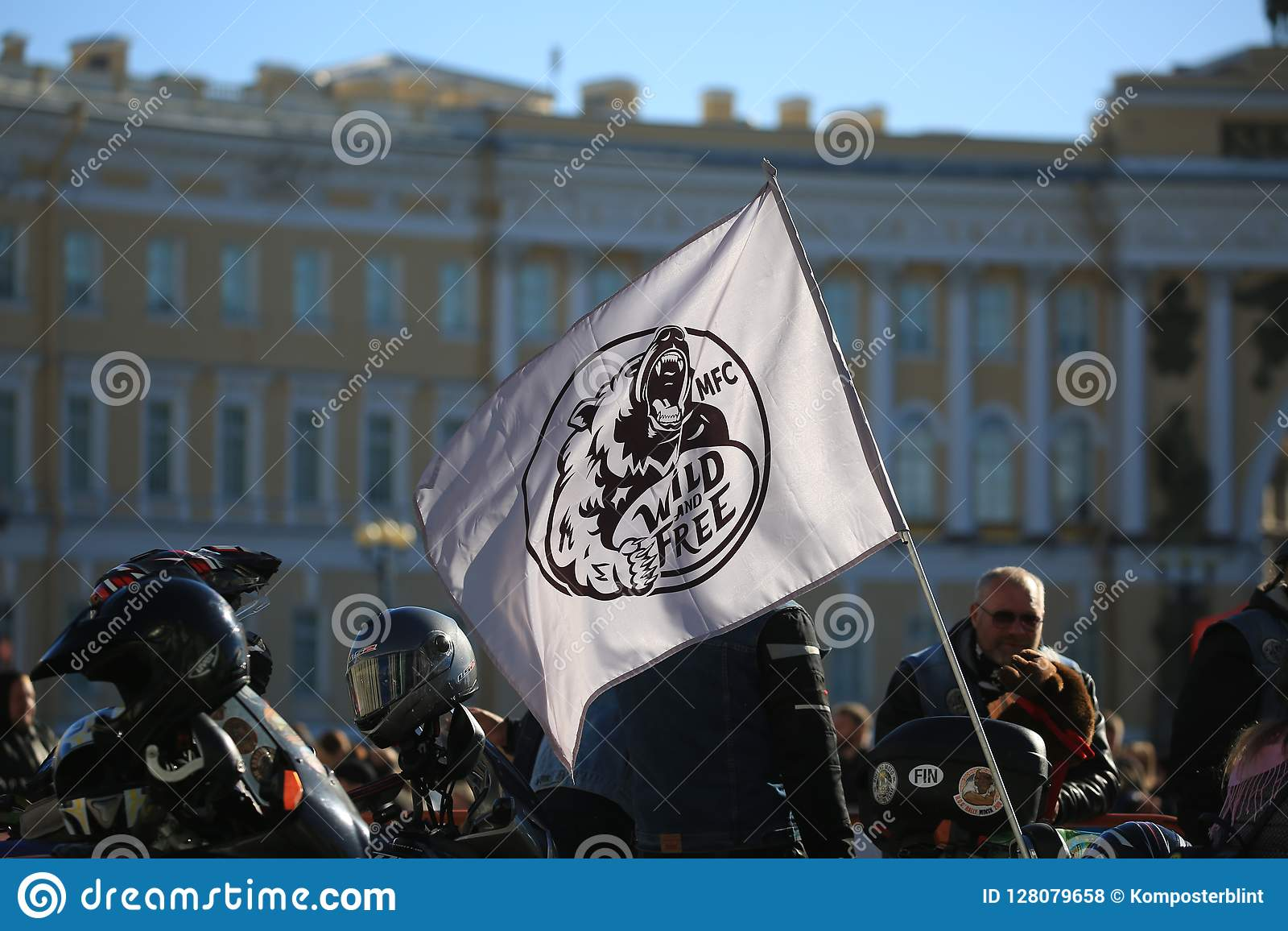 Folk och flagga av den lösa och fria motofanatsklubban mot bakgrunden av byggnaden för allmän personal