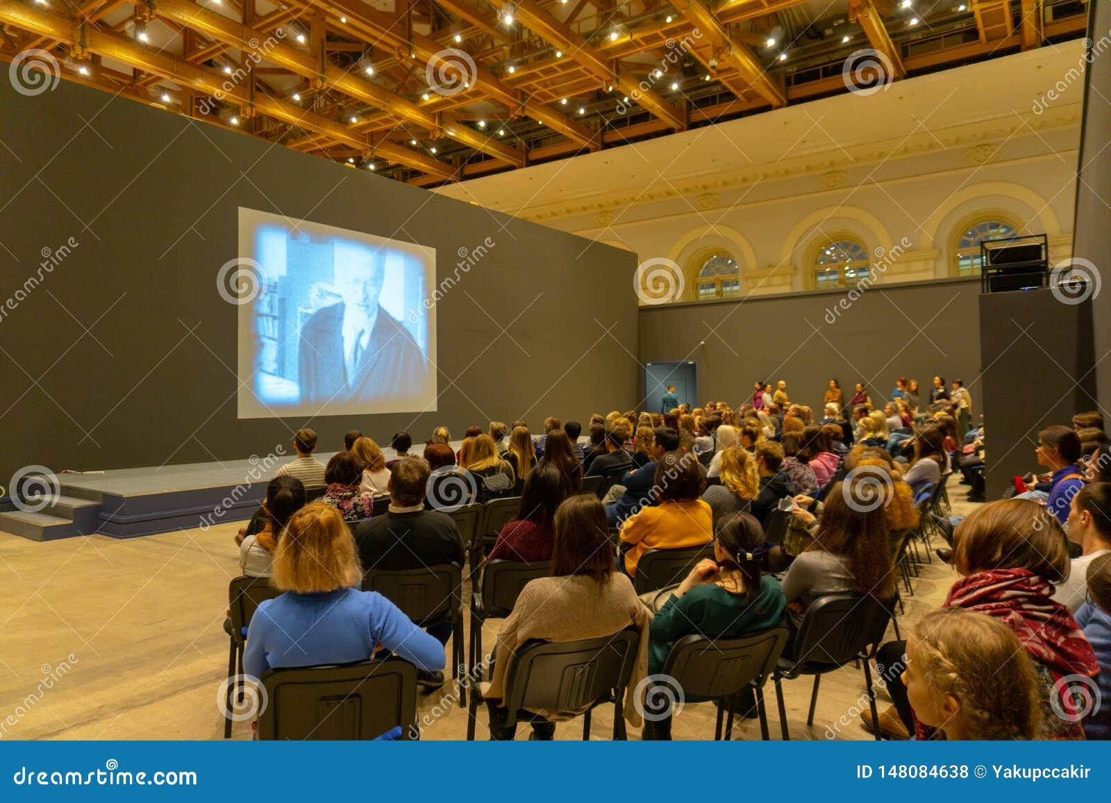 Folk på konferensen av historia som lyssnar och håller ögonen på skärmen tillbaka sikt Horisontalbildsammans?ttning