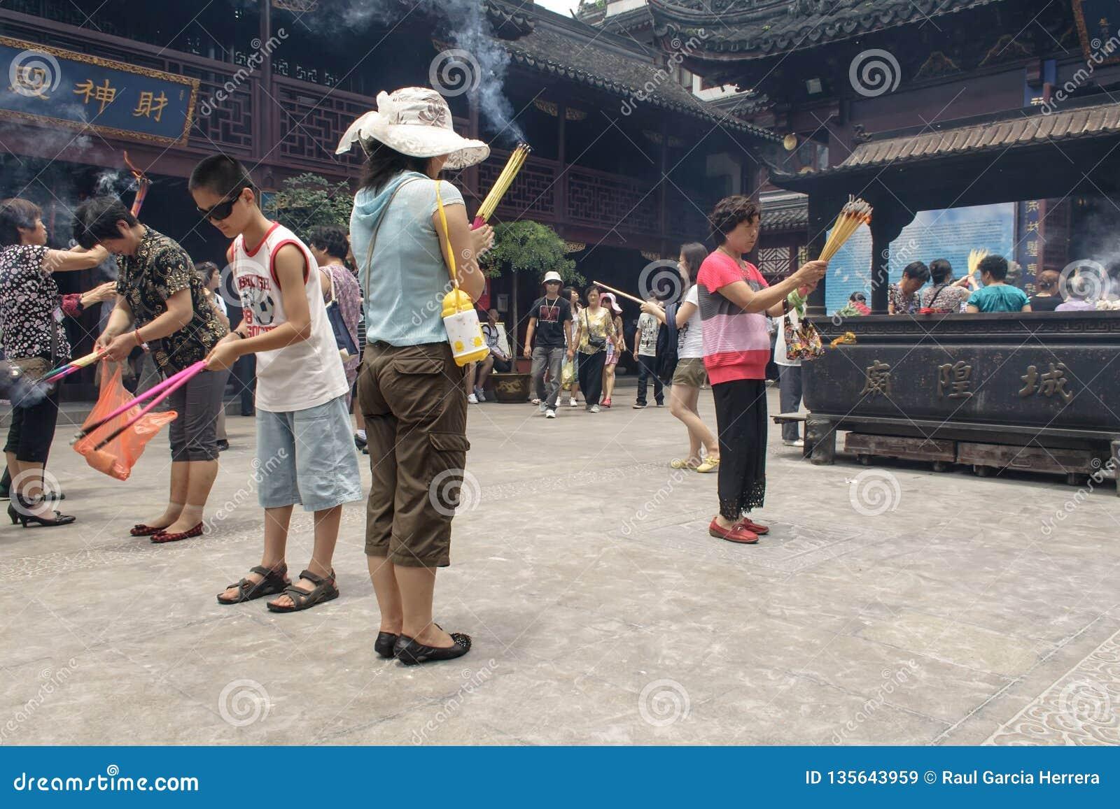 Folk som ber i stadsgudtemplet Chenghuang Miao på staden av Shanghai i Kina
