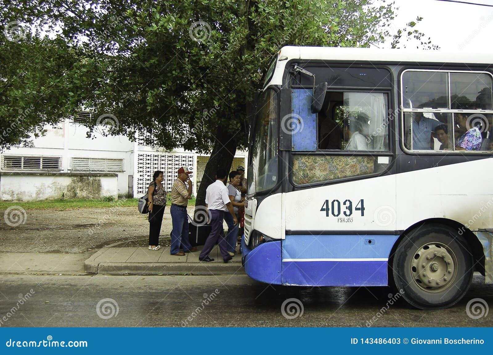 Folk som får på bussen i havana