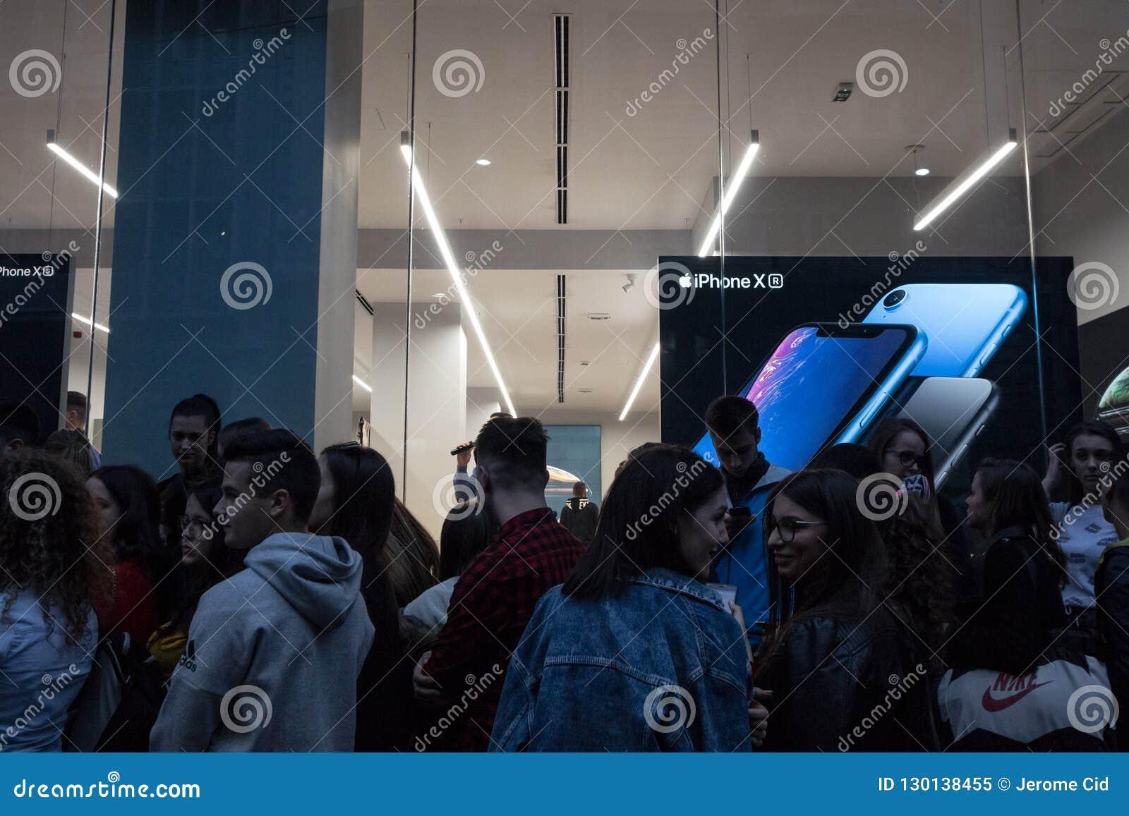 Folk som framme väntar av det Apple Store fönstret för lanseringen av den nya Apple Smartphone, Iphonen XR, på skymning