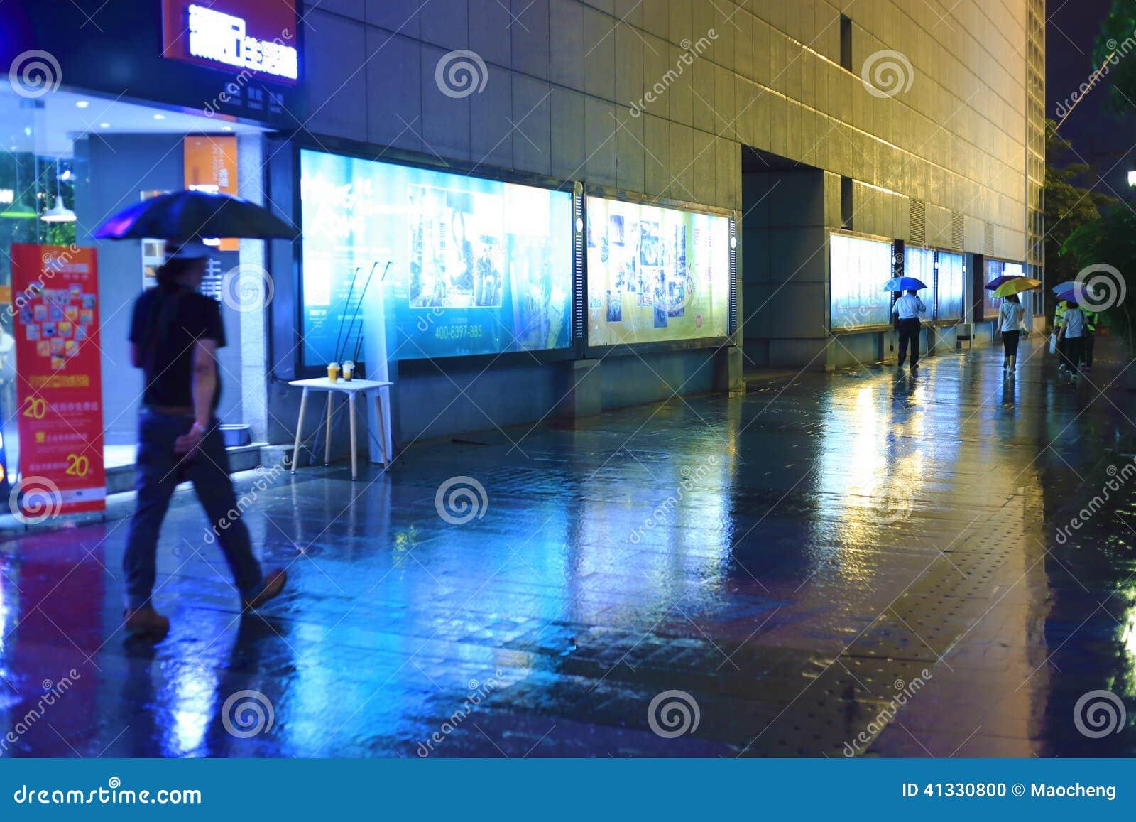 Folk som går i regn på natten