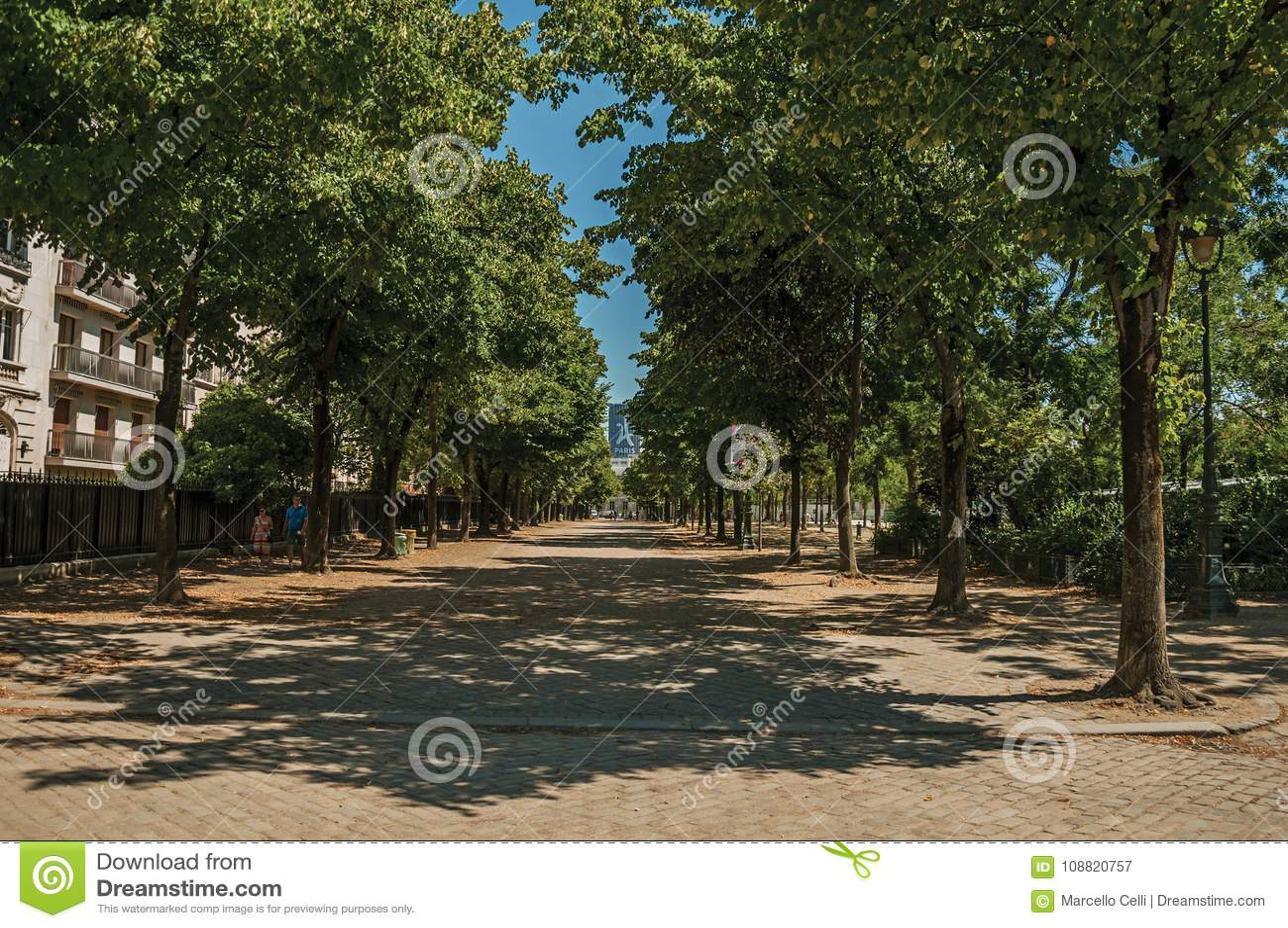 Folk som går på trottoaren med träd på en solig dag i Paris