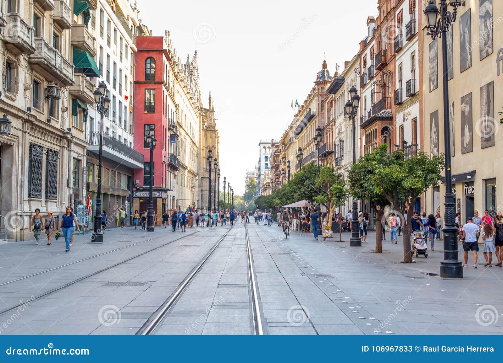 Folk som går under dagen i en fot- gata nära domkyrka i Seville, Spanien berömd landmark
