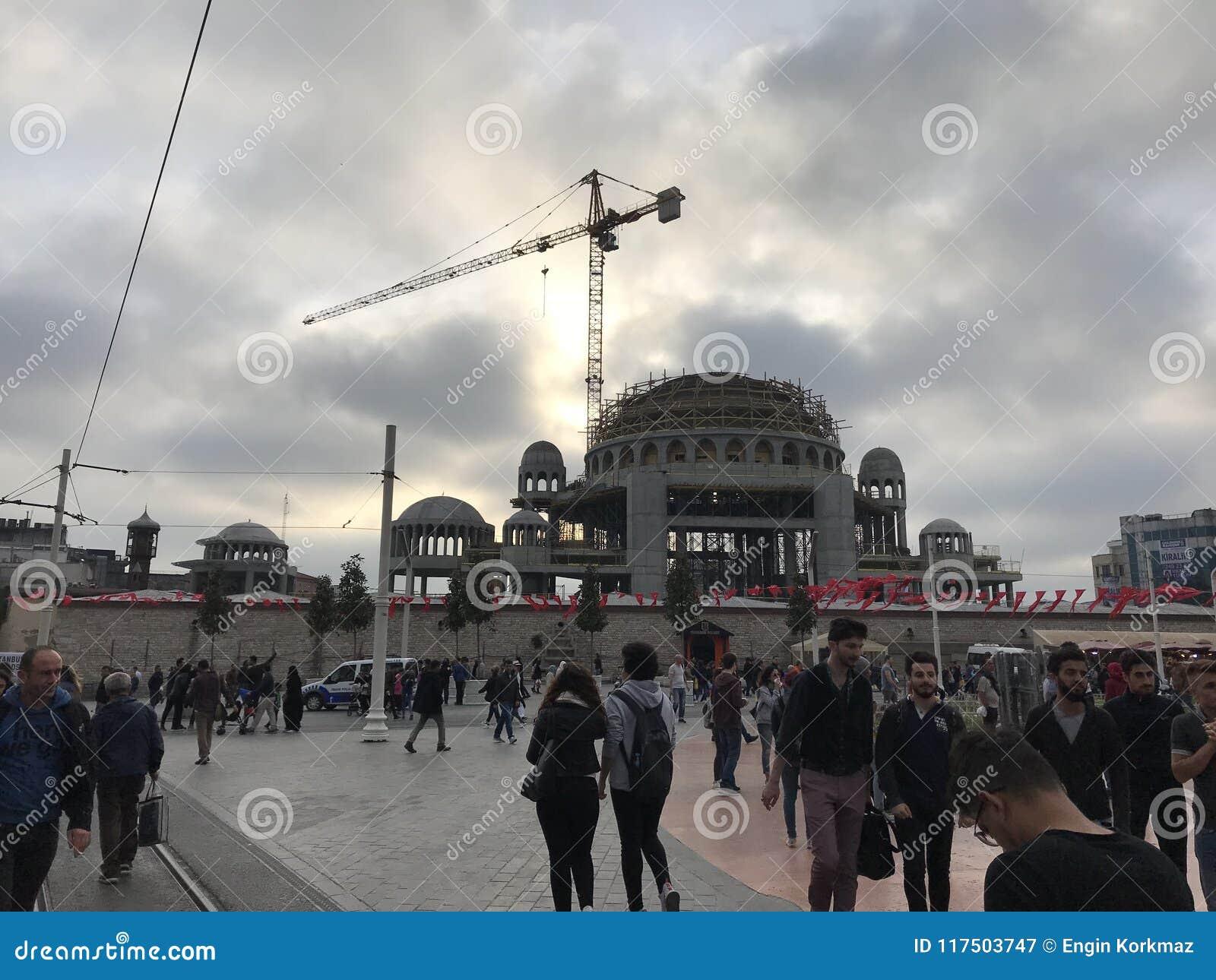 Folk som omkring går, och bilar i trafik på den Taksim fyrkanten, Istanbul