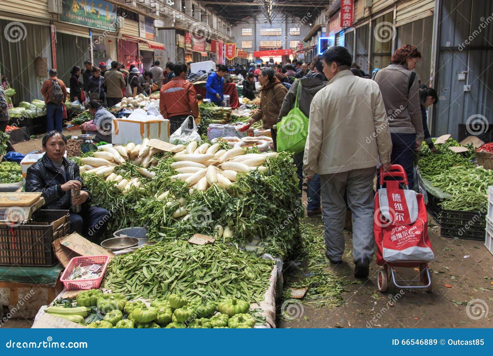 Folk som säljer och köper i en traditionell marknad i mitten av Kunming
