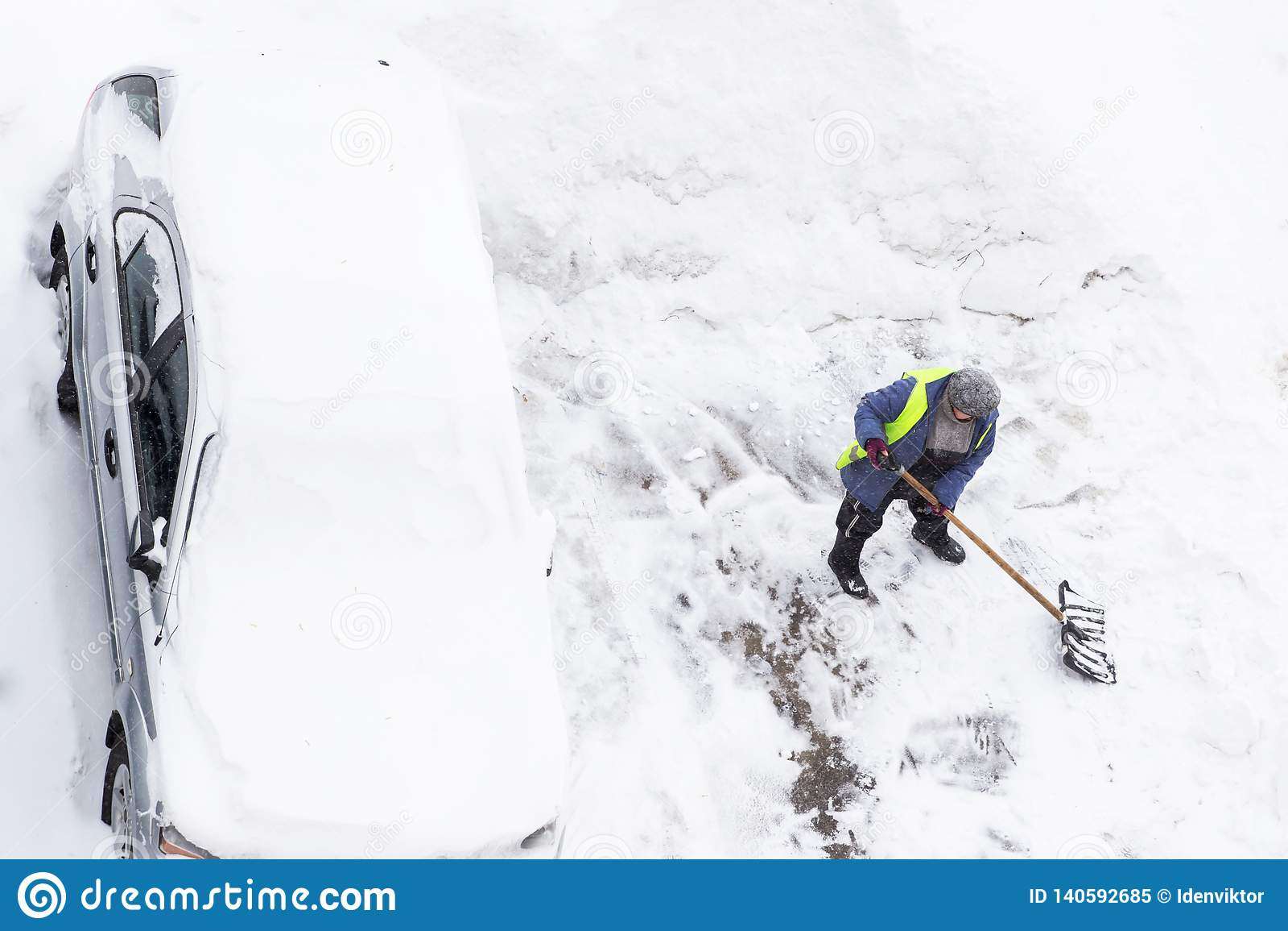 Folk som skyfflar snö nära bilen på parkering Snörensning efter ett tungt snöfall