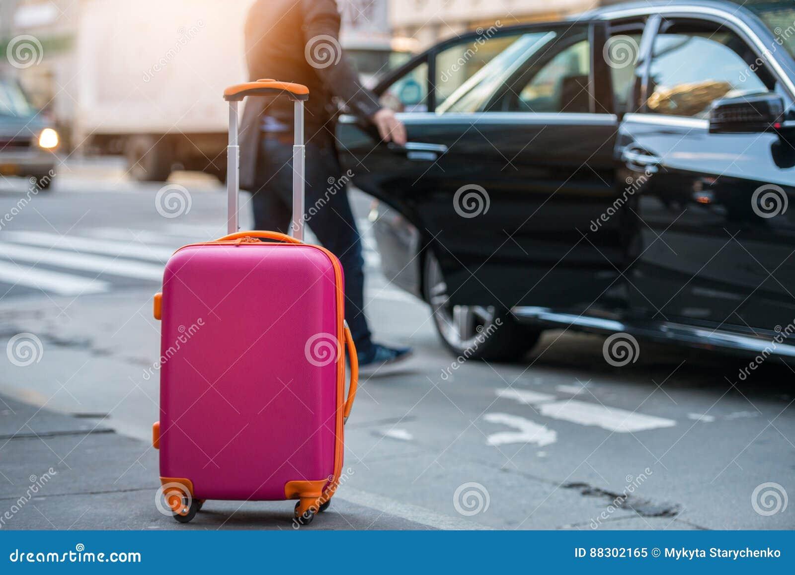 Folk som tar taxien från en flygplats och laddar handbagagebagagepåsen till bilen
