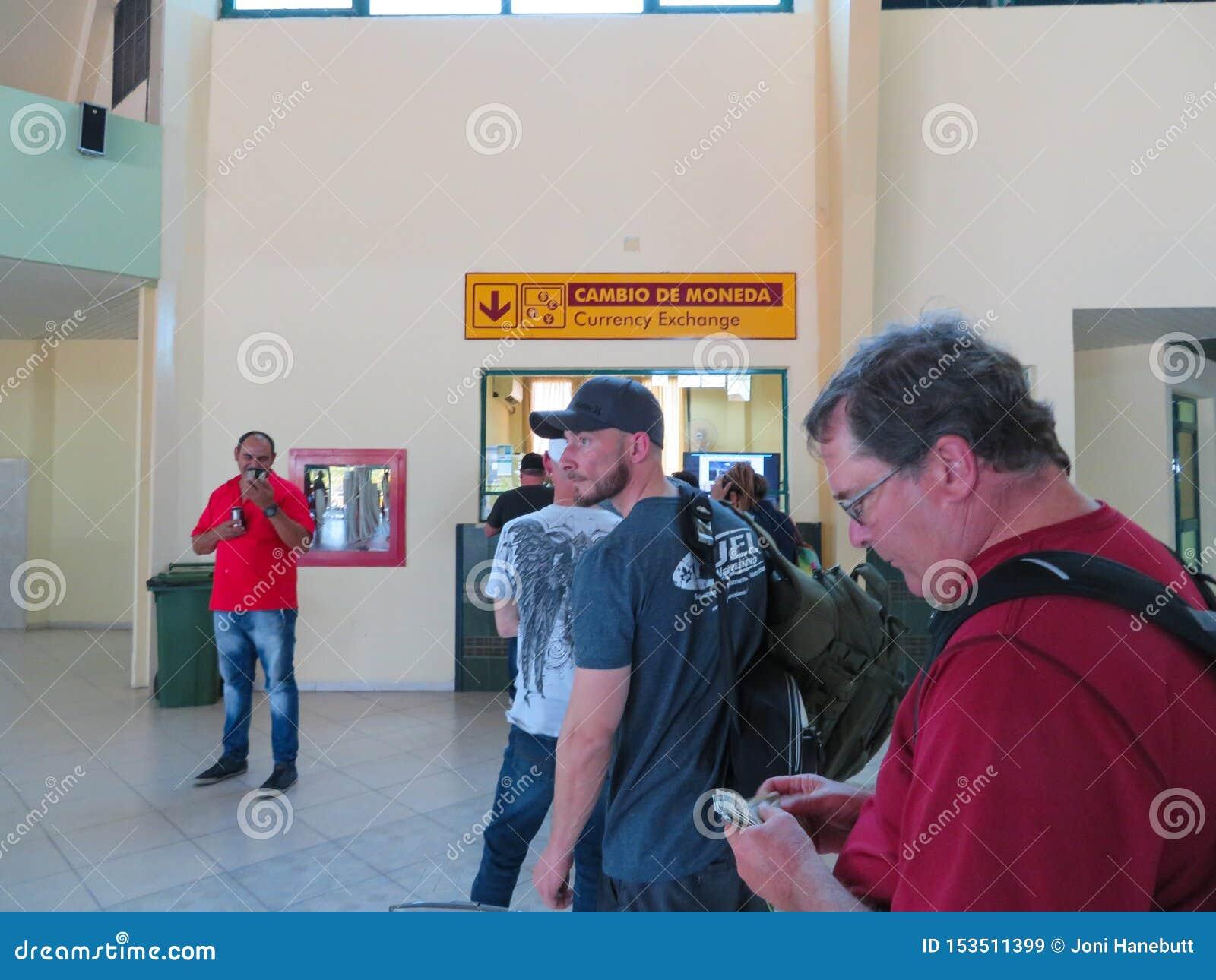 Folk som väntar i linje på den Holguin flygplatsen för att utbyta deras valuta