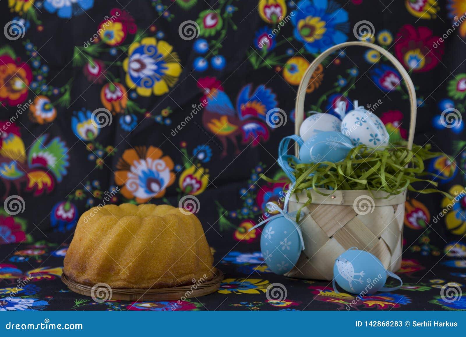 Folk stileaster garnering med vita och blåa ägg på målad textilbakgrund