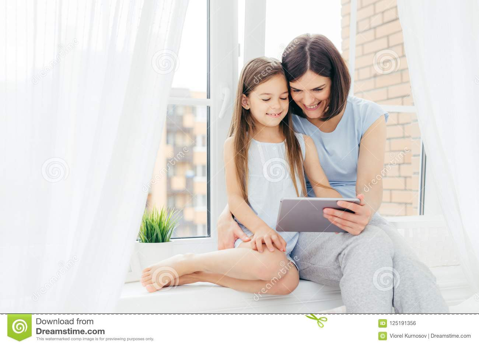 Folk teknologi, familj, barnbegrepp Den positiva unga annan och hennes lilla dottern sitter på fönsterfönsterbrädan, digital minn