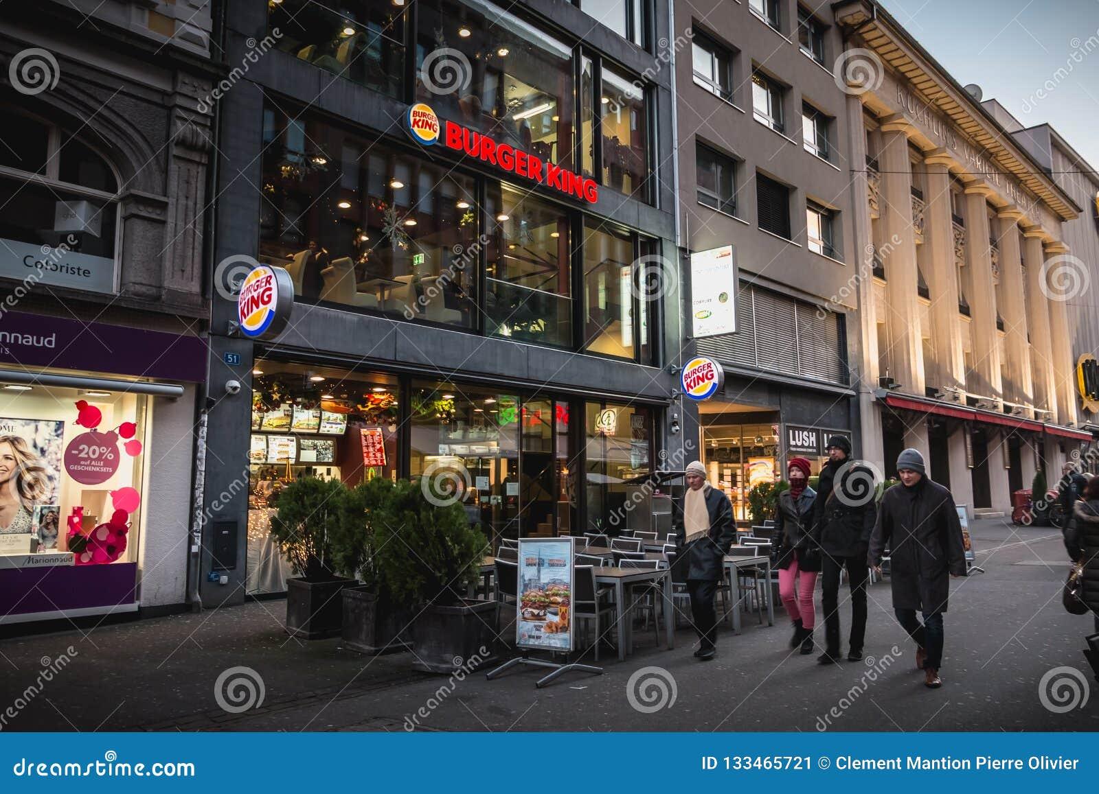 Folket går främst av Burger King i den shoppa pedestrien