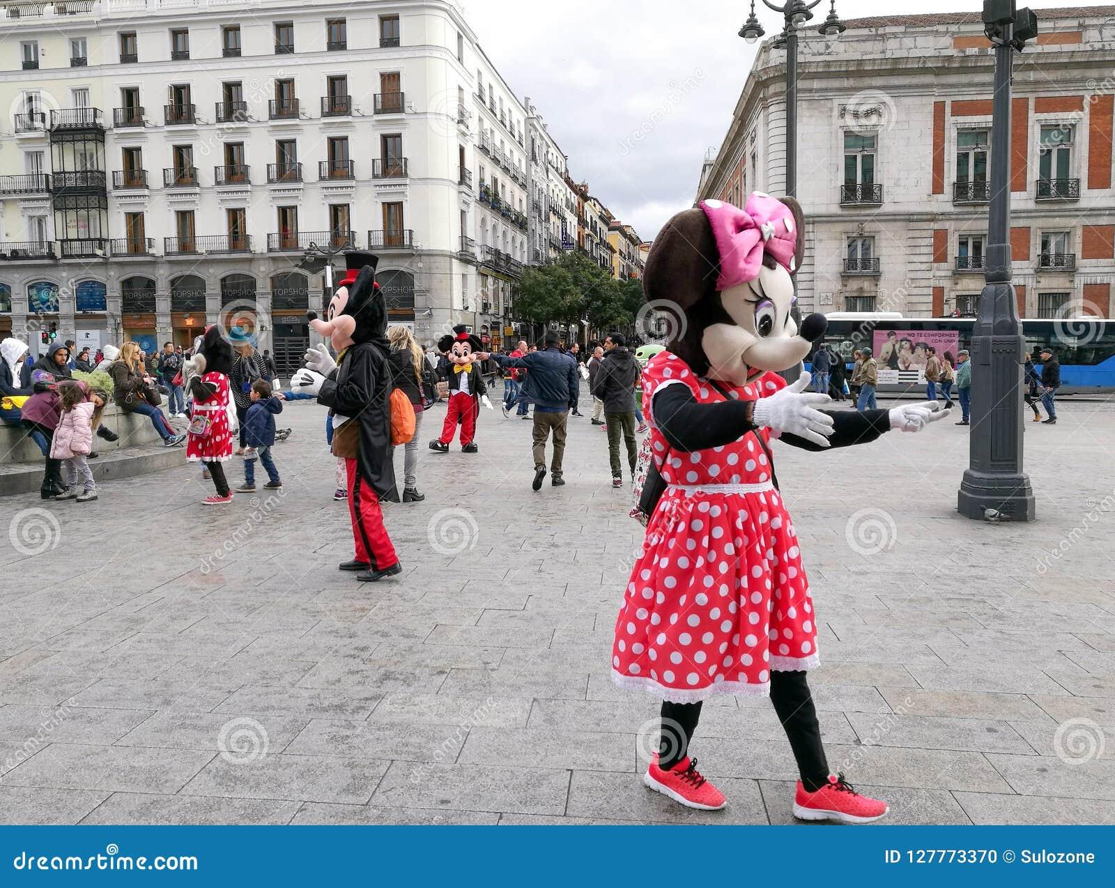 Folket i dräkter av Minnie och Mickey Mouse går för att underhålla turister