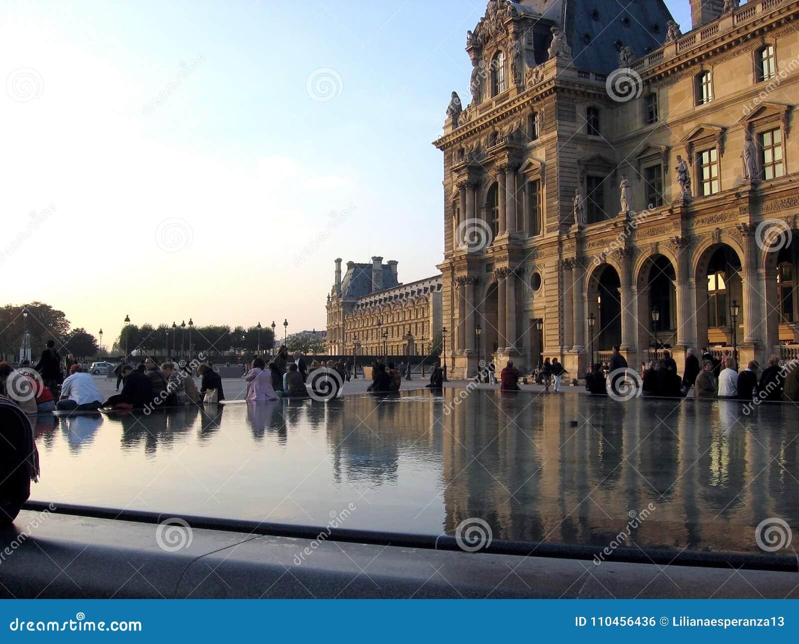Folket i Louvremuseet Paris Frankrike reflekteras i vattnet av springbrunnen Paris Frankrike