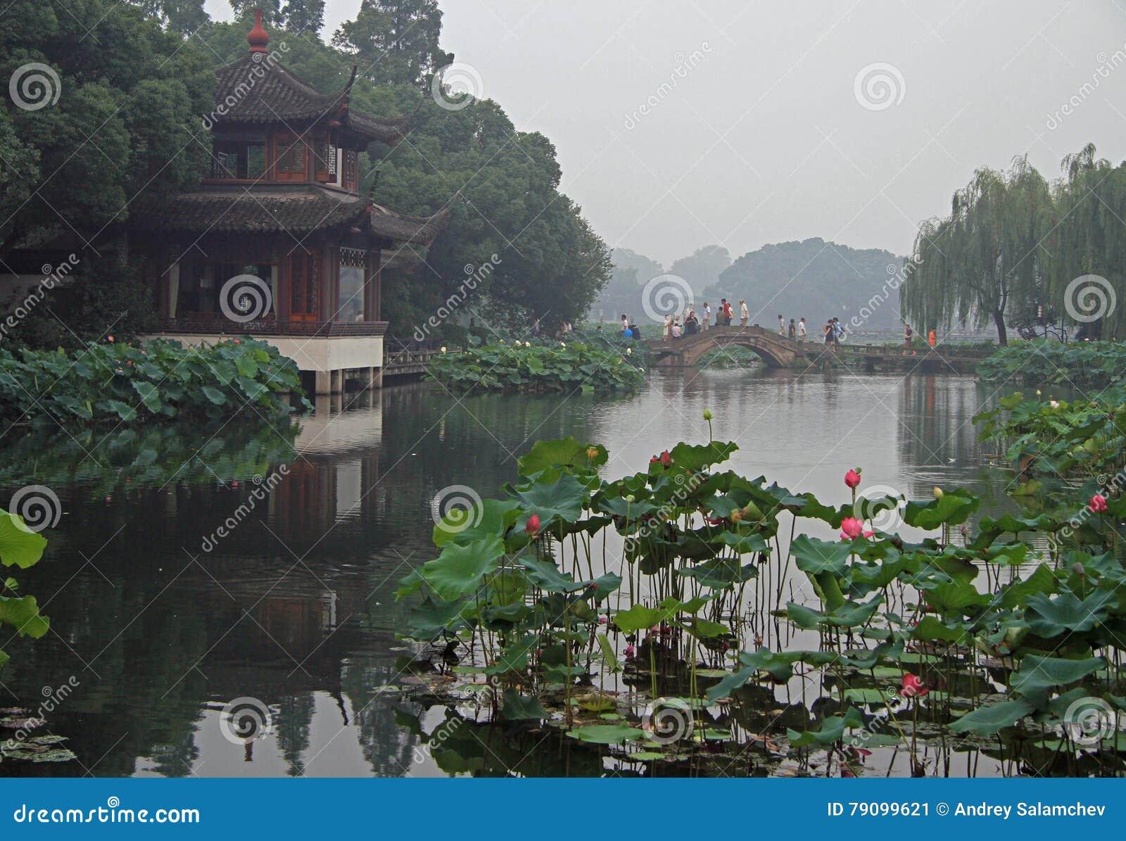 Folket korsar den västra sjön i Hangzhou vid bron