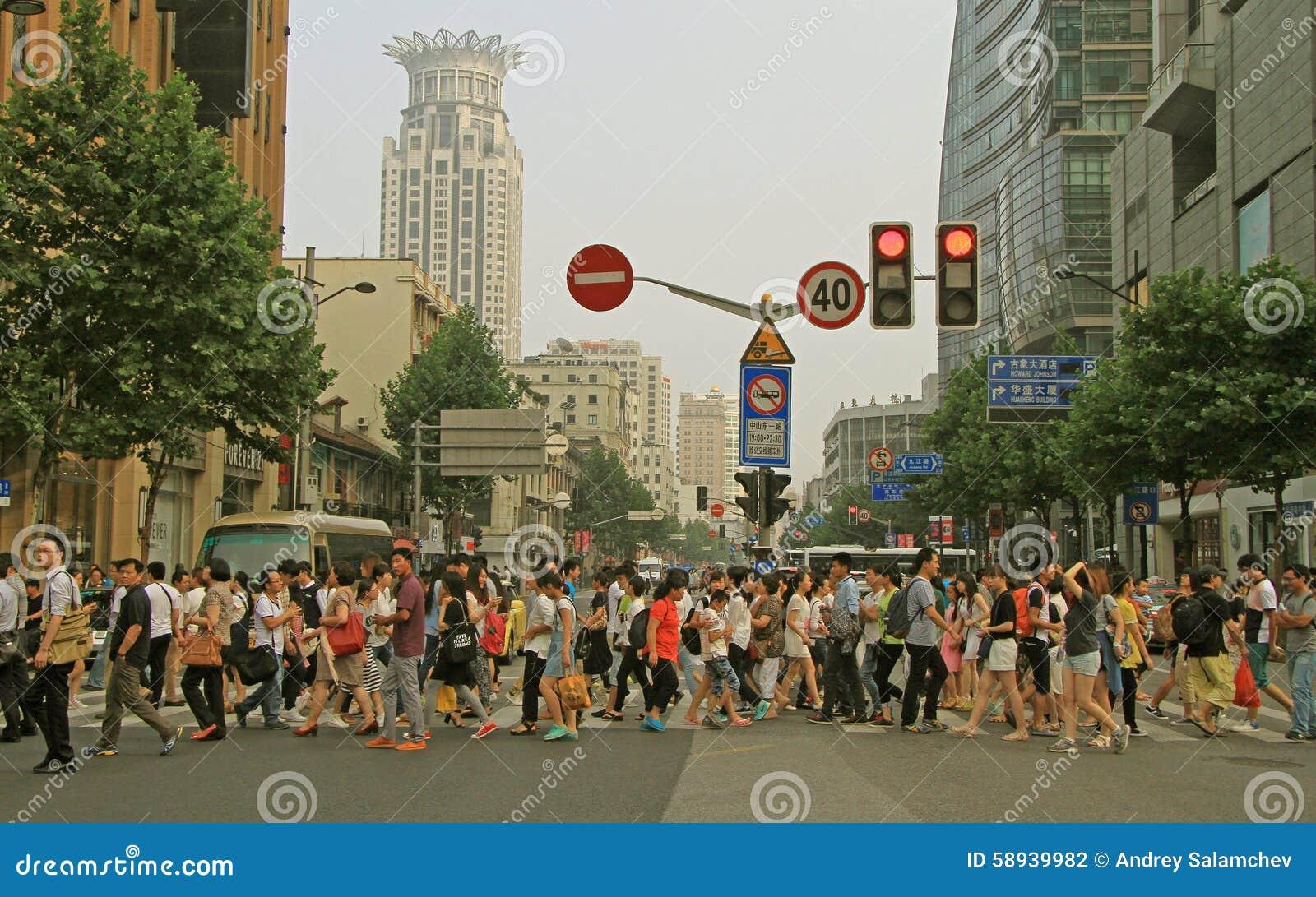 Folket korsar vägen vid övergångsställe i Shanghai