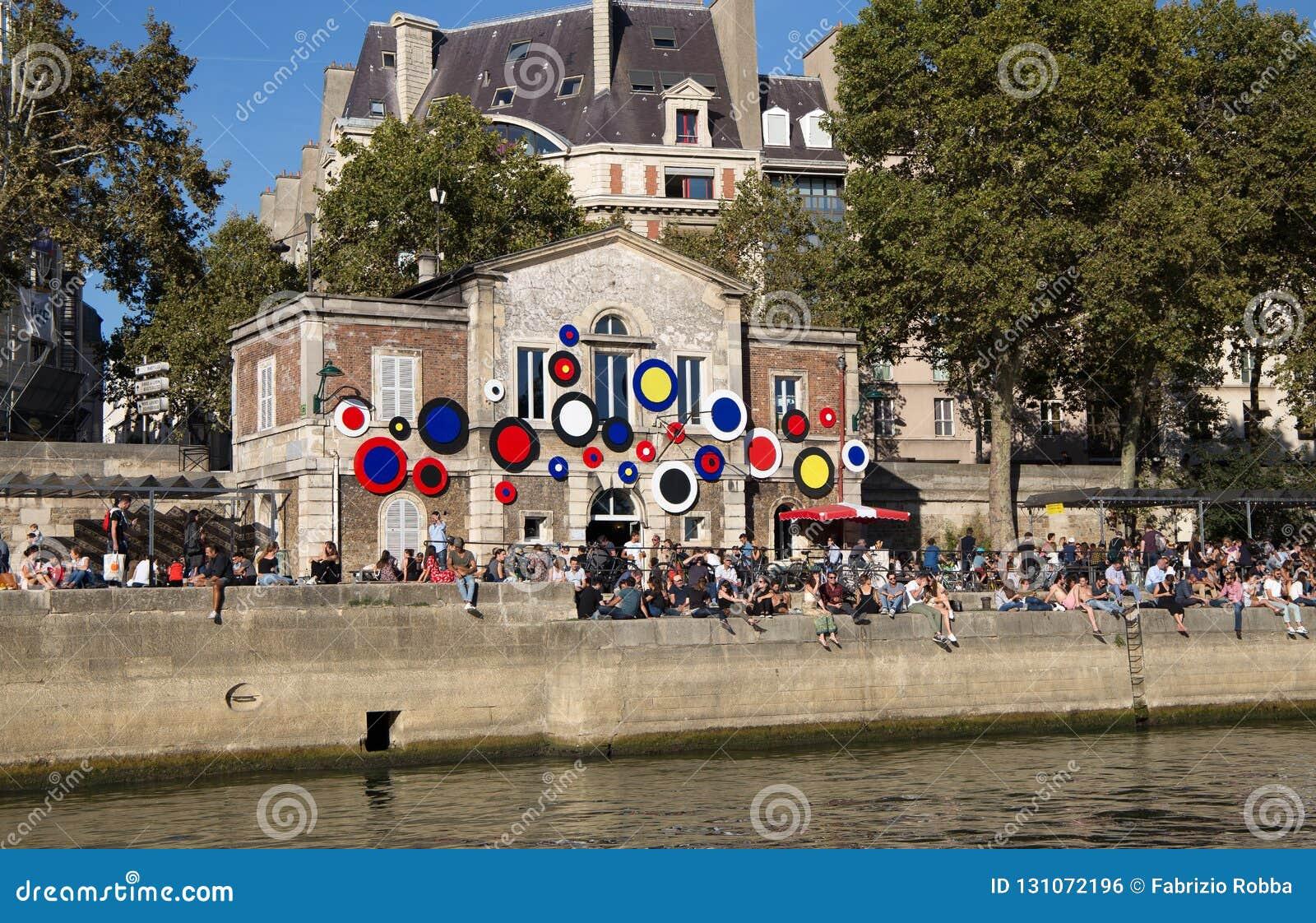 Folket sitter längs kusterna av floden Seine i en solig dag i Paris, Frankrike