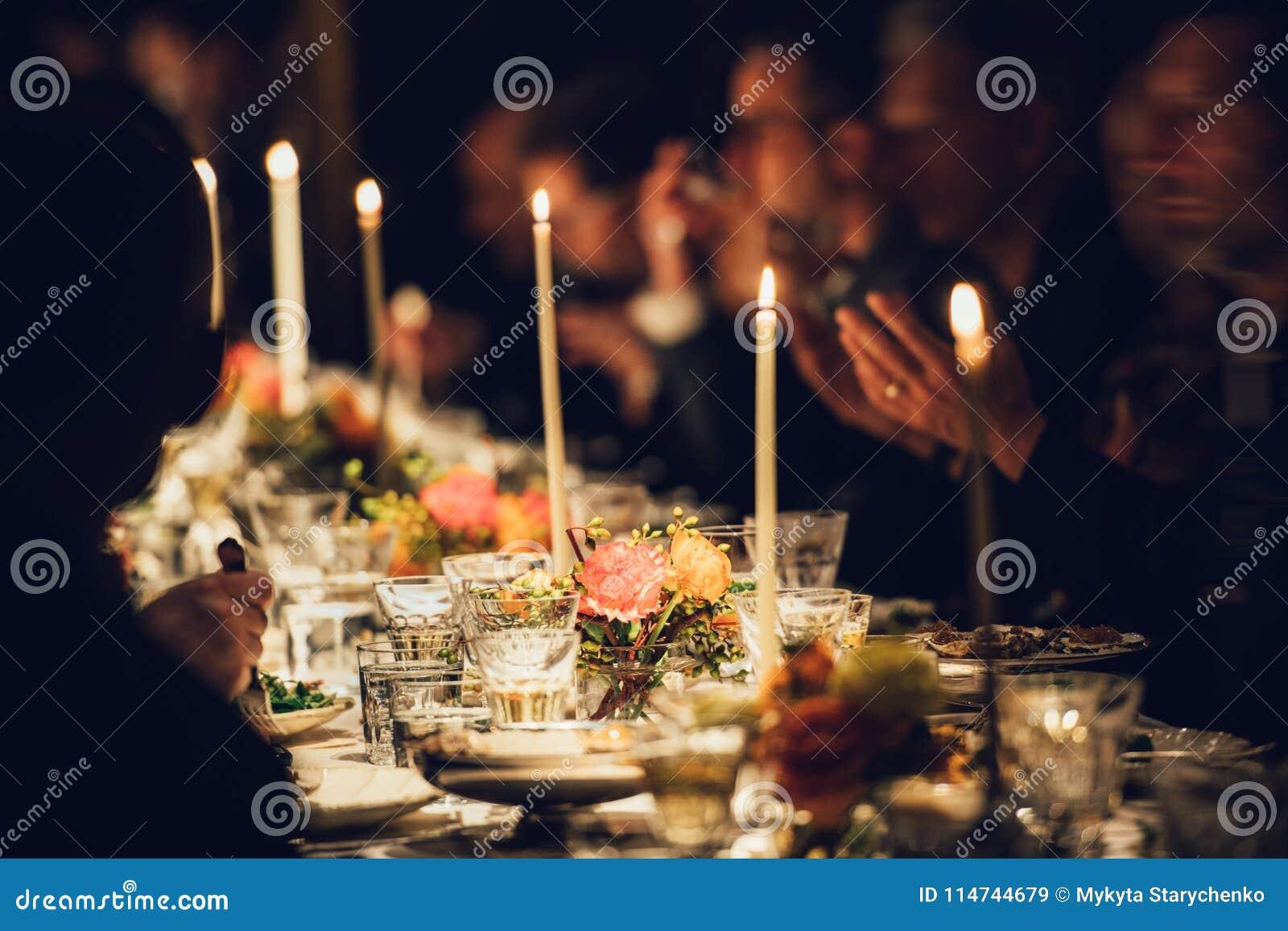 Folket tycker om en familjmatställe med stearinljus Stor tabell som tjänas som med mat och drycker