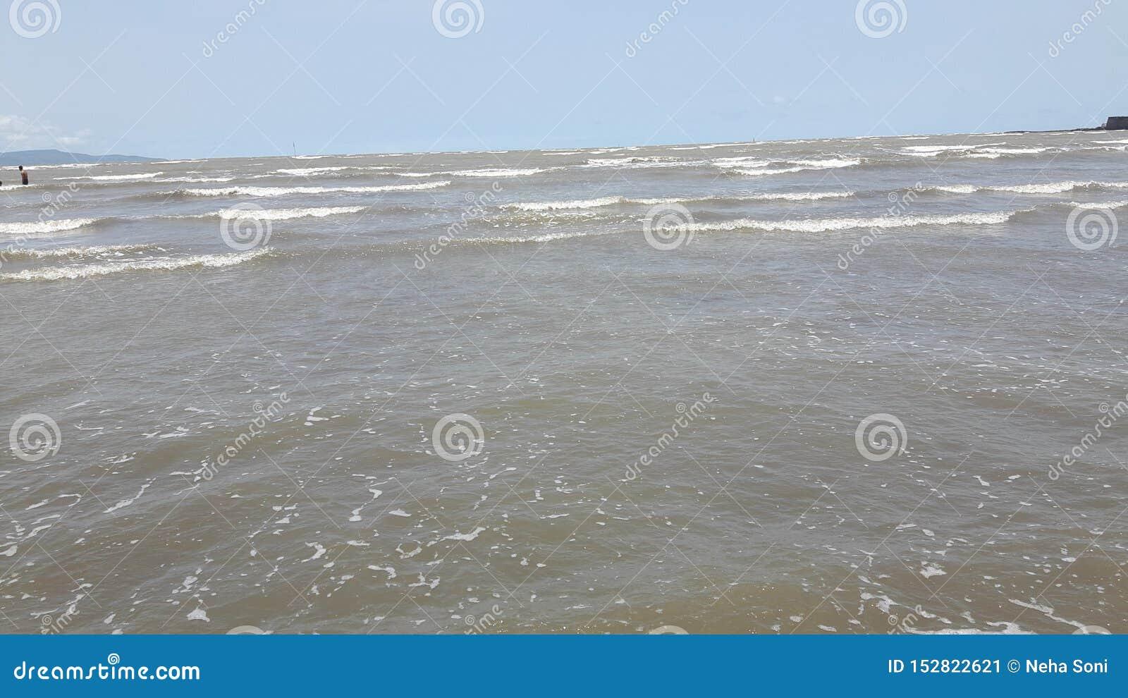 Folket tycker om strandplatsen med blå himmel och molnen
