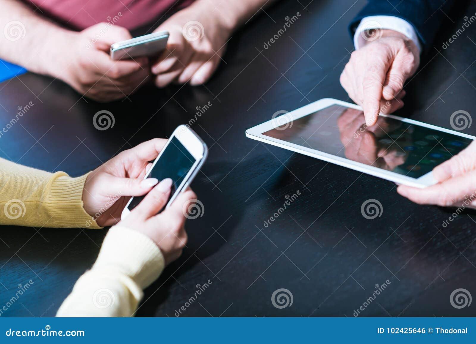 Folkhänder genom att använda mobiltelefoner och den digitala minnestavlan