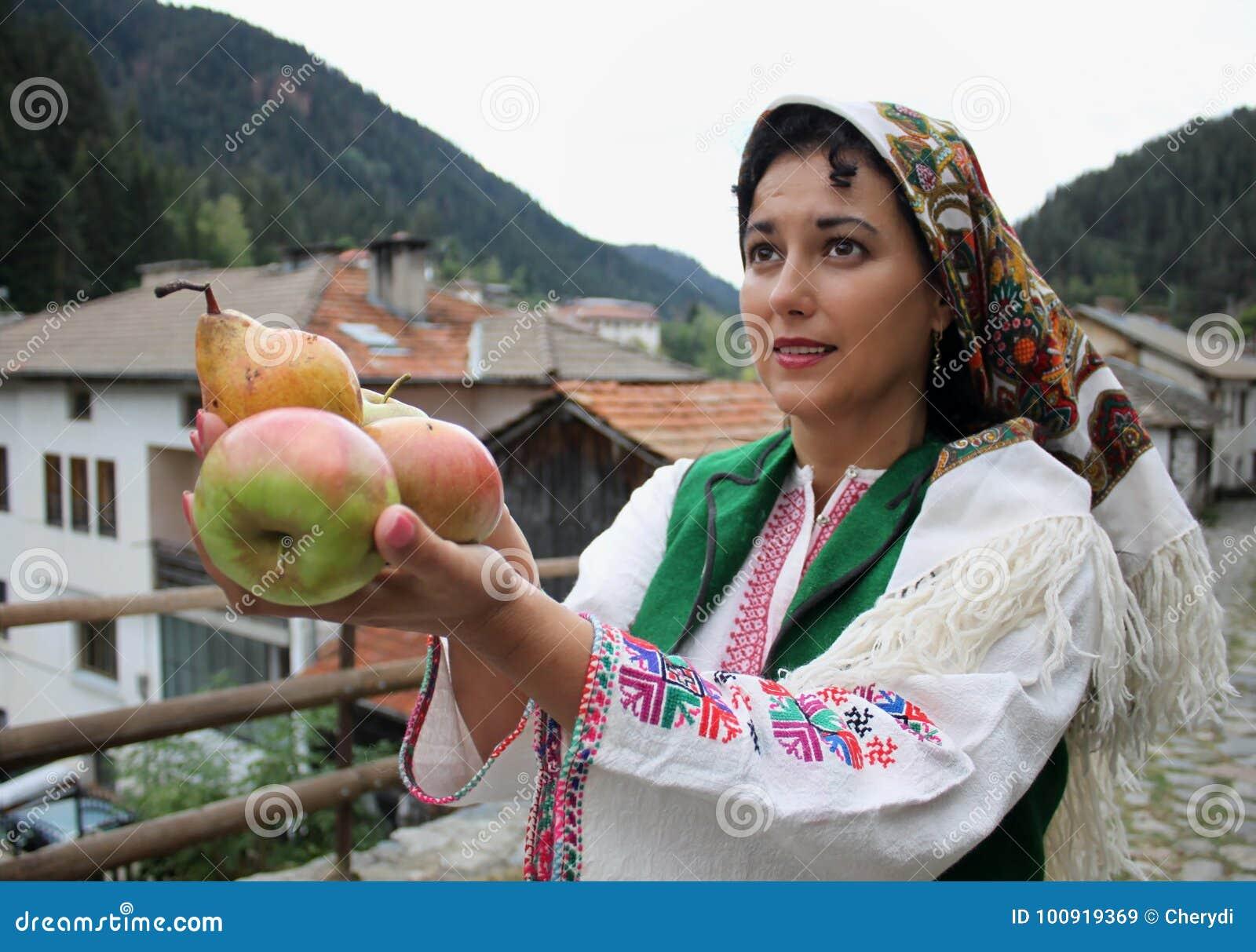 Une belle jeune femme dans le costume bulgare traditionnel de folklore  tient le fruit frais e376e890c19