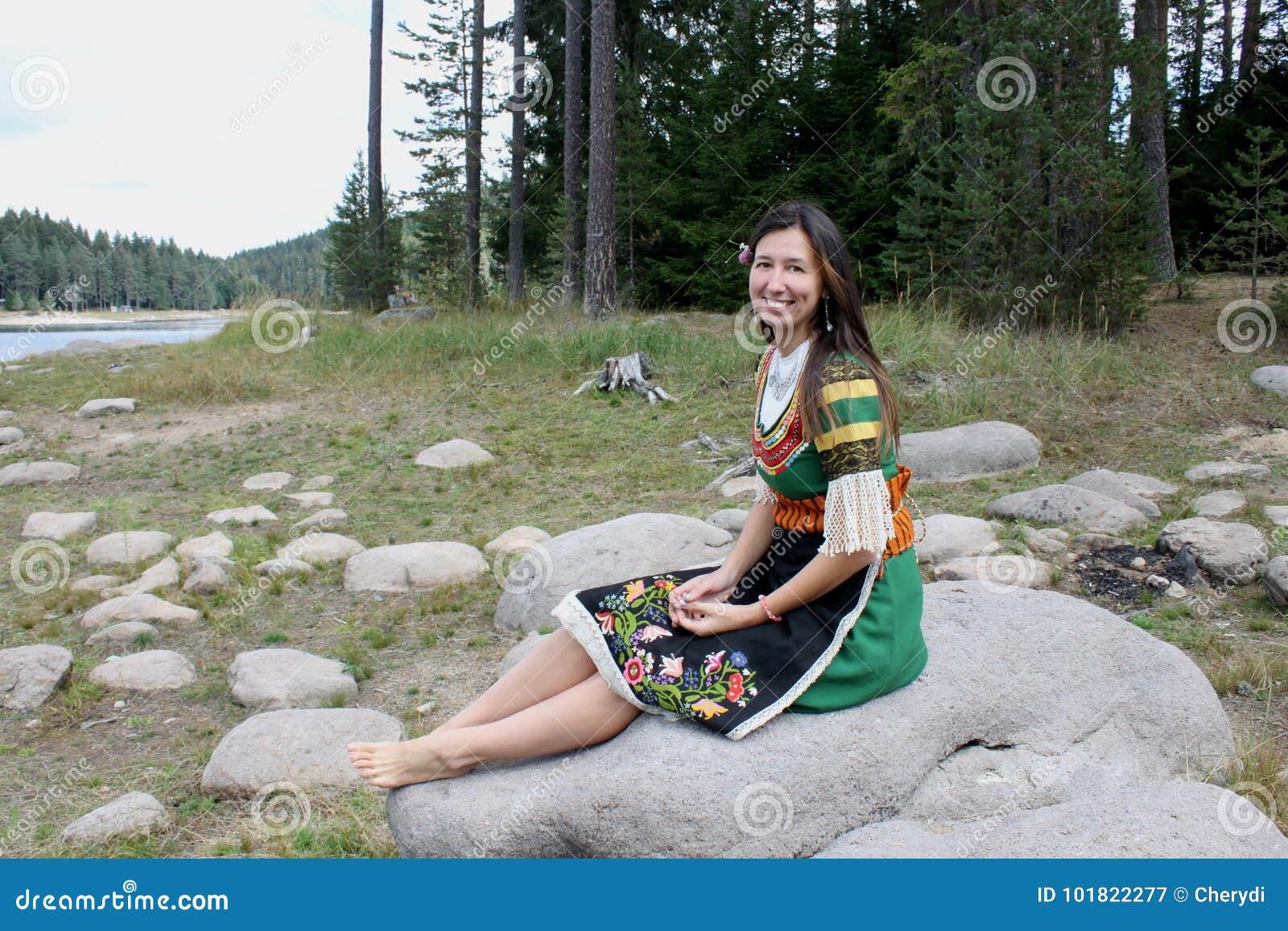 Une belle jeune femme dans le costume bulgare traditionnel de folklore  s assied sur une pierre près d un lac 0345a010f06