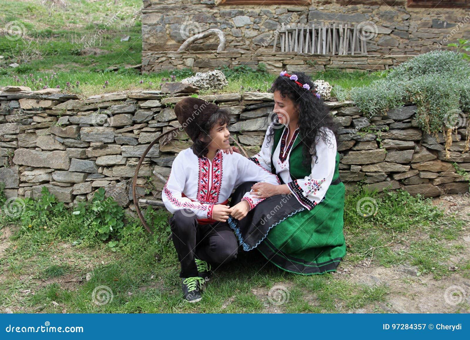 Les belles jeunes femmes et un garçon beau dans des costumes de folklore  ont tiré dans le vieux village de Leshten, Bulgarie 3a22c82d8e8