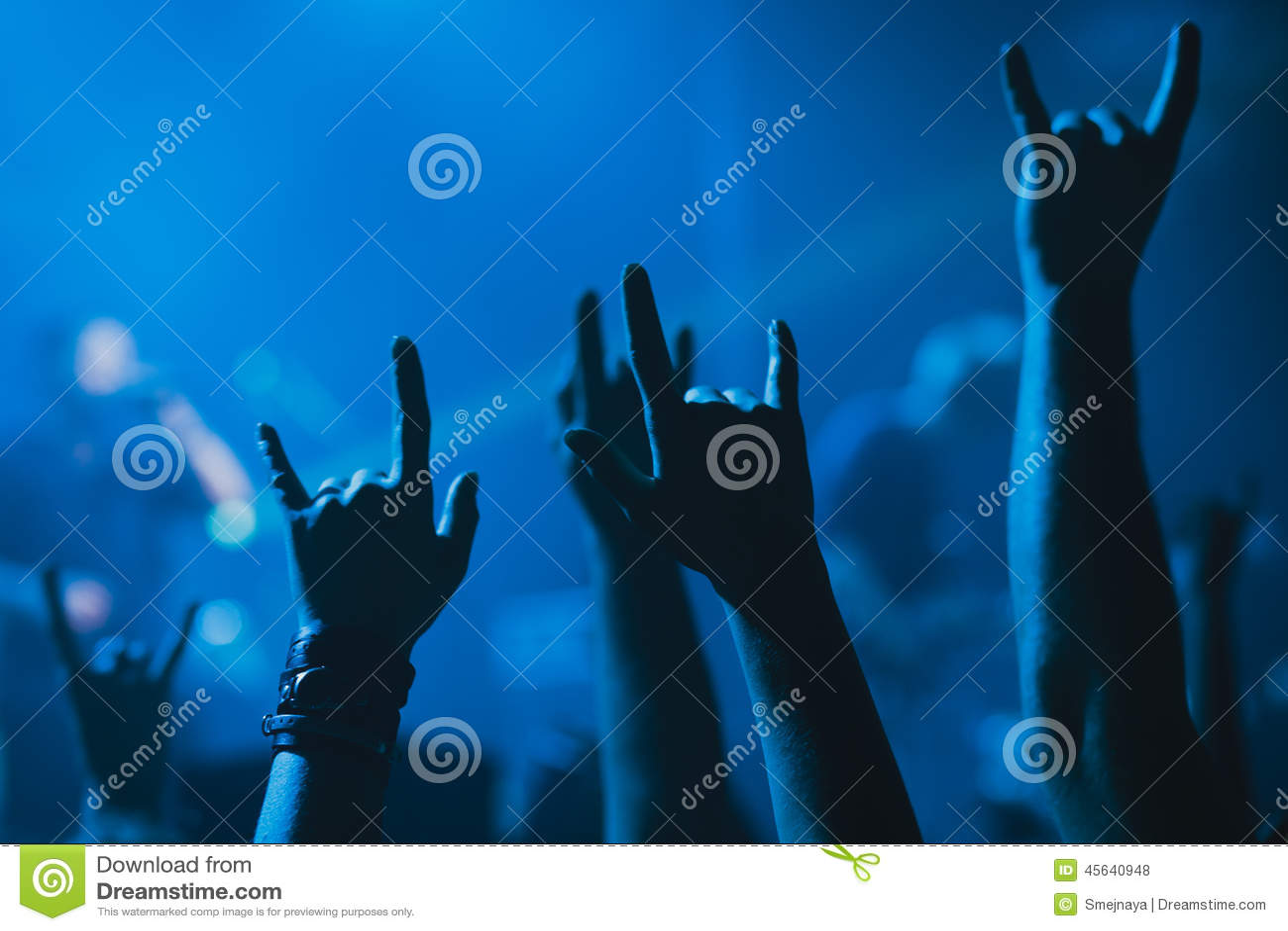 Folkmassa som hurrar och håller ögonen på en musikband på etapp