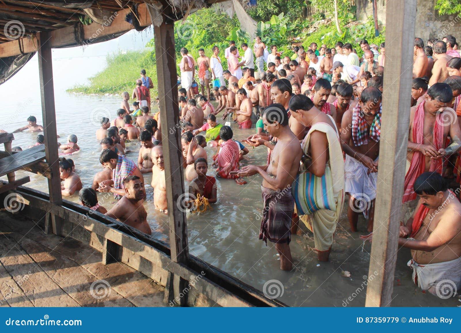 Folkmassan av hinduiskt vallfärdar monterar på packar ihop av floden och ber för sena förfäder