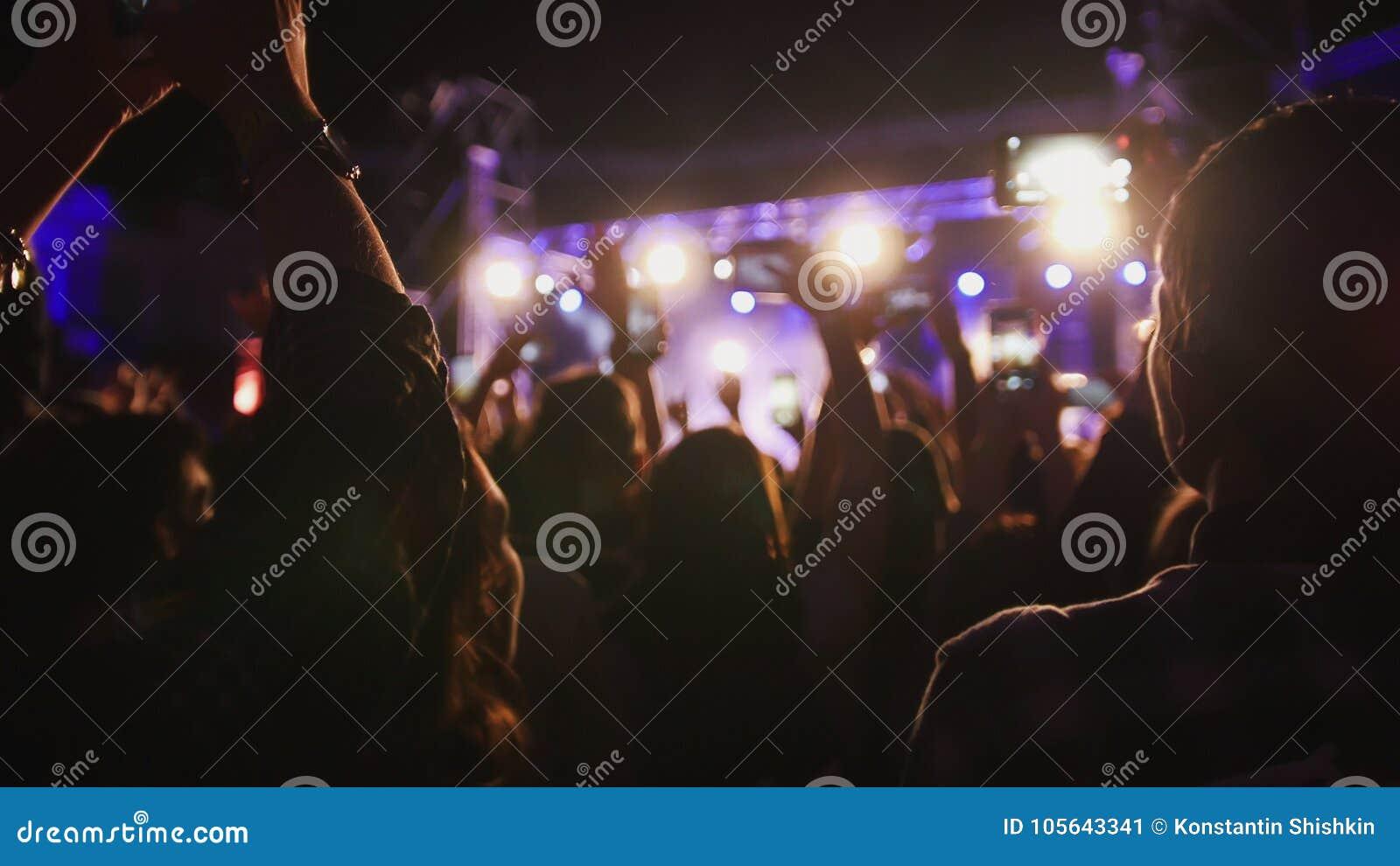 Folkmassan av skuggor av folk som dansar på konserten