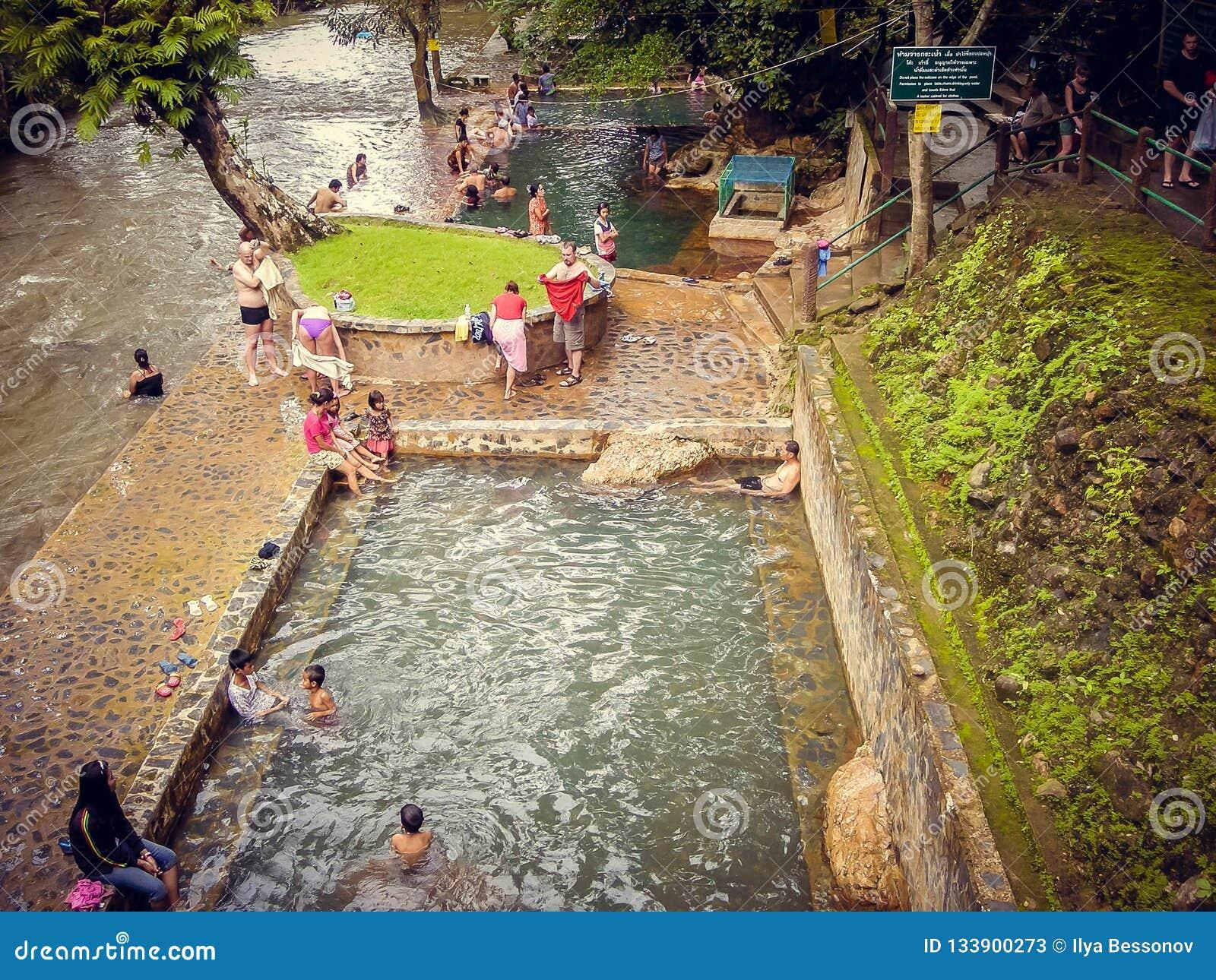 Folkturister simmar i pölen som är naken i Thailand
