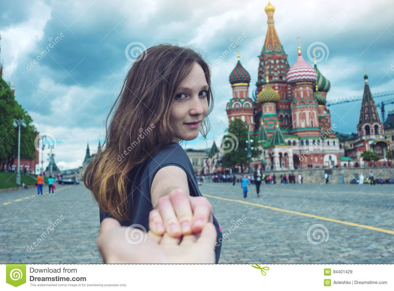 Follow me, Attractive brunette girl holding the hand leads to the red square in Moscow. Russia.
