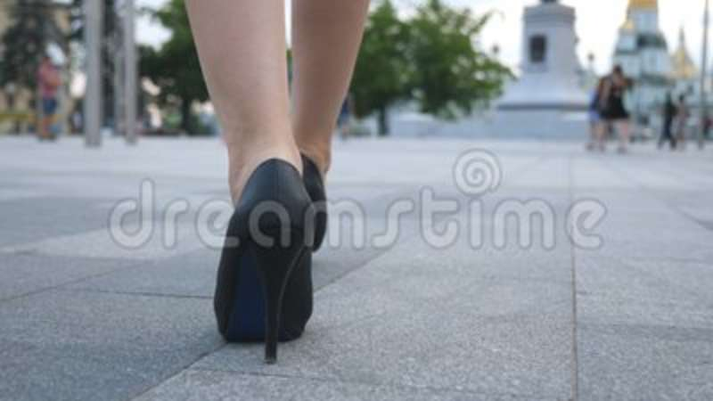 65737220210 Follow to female legs in high heels shoes walking in urban street. Feet of  young business woman in high-heeled footwear.