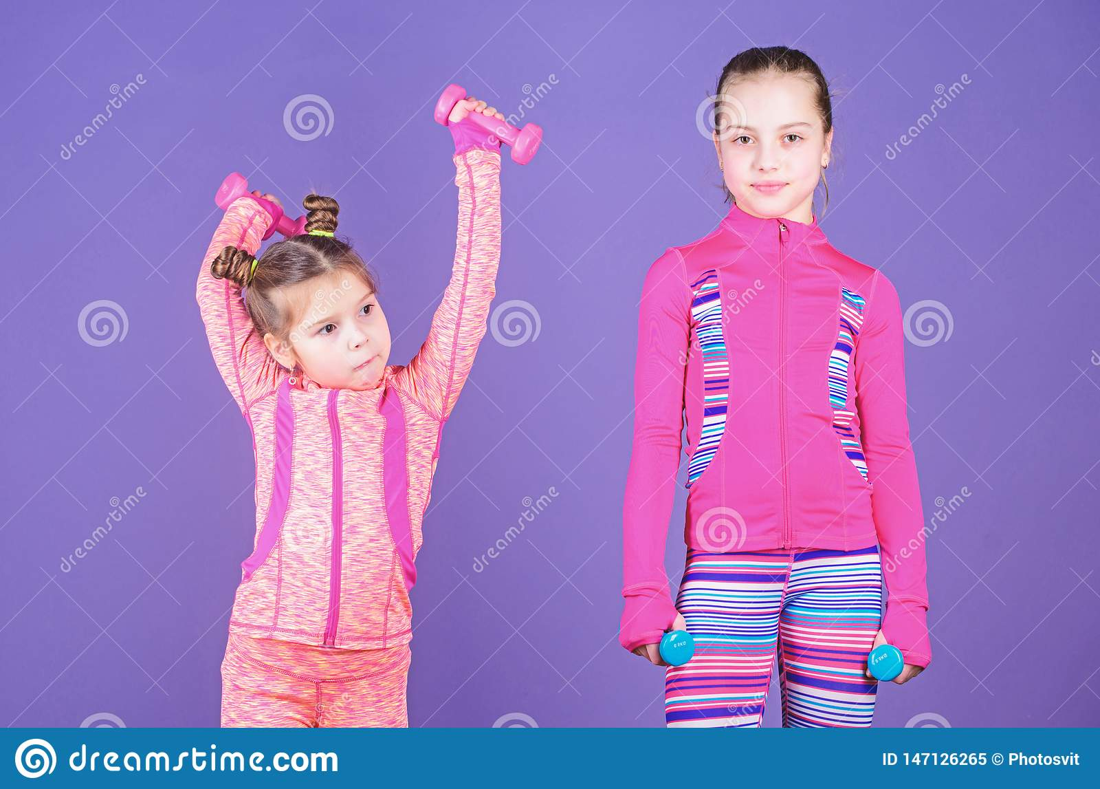 Following her sister. Girls cute kid exercising with dumbbells. Motivation and sport example concept. Toddler repeat