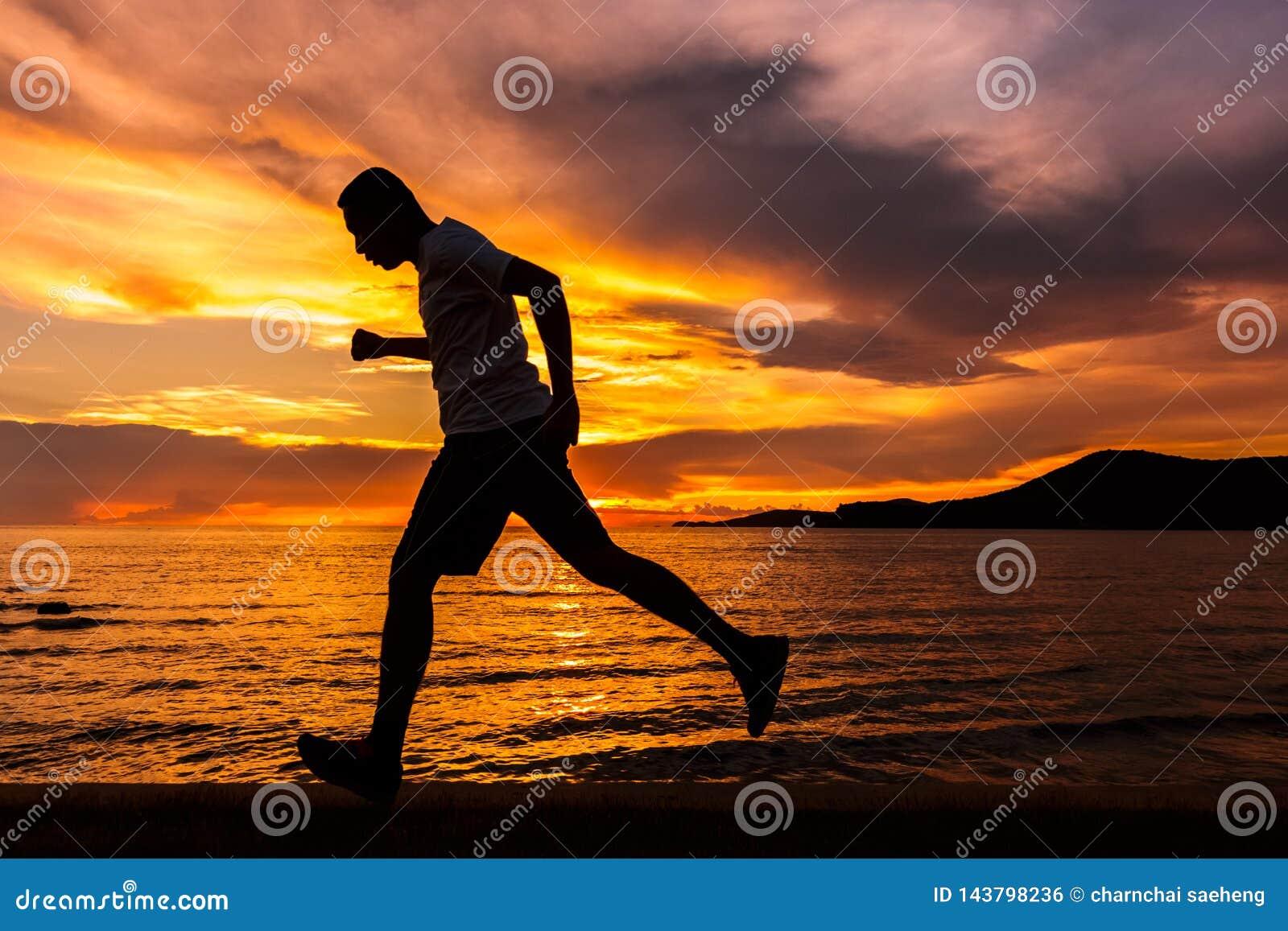 Fonctionnement d homme à l île et à lui courant près de la plage avec le coucher du soleil et le beau ciel avec le nuage gentil