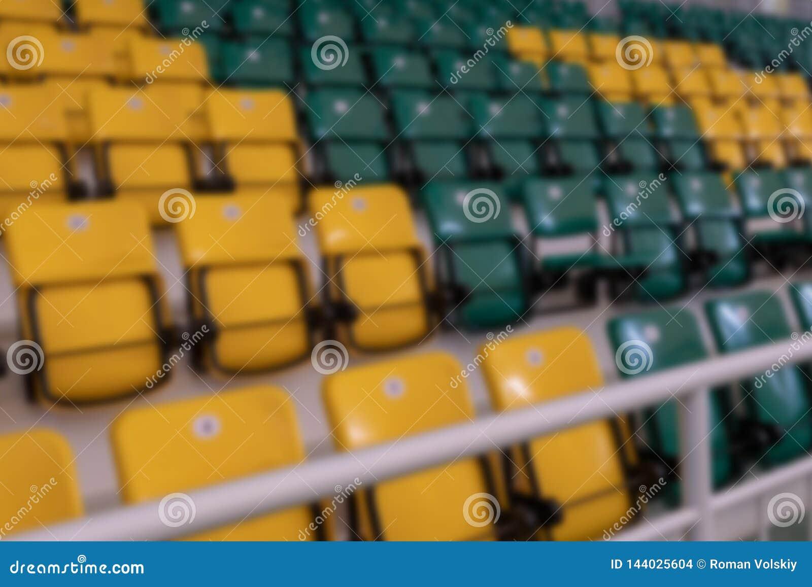 Fond brouillé Sembler la personne malvoyante Sièges en plastique jaunes et verts dans les supports du complexe de sports