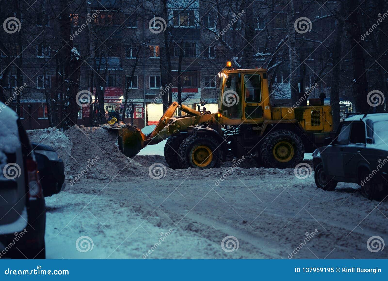 Fond brouillé Tache floue de lumières de ville de nuit Véhicule de déblaiement de neige enlevant la neige