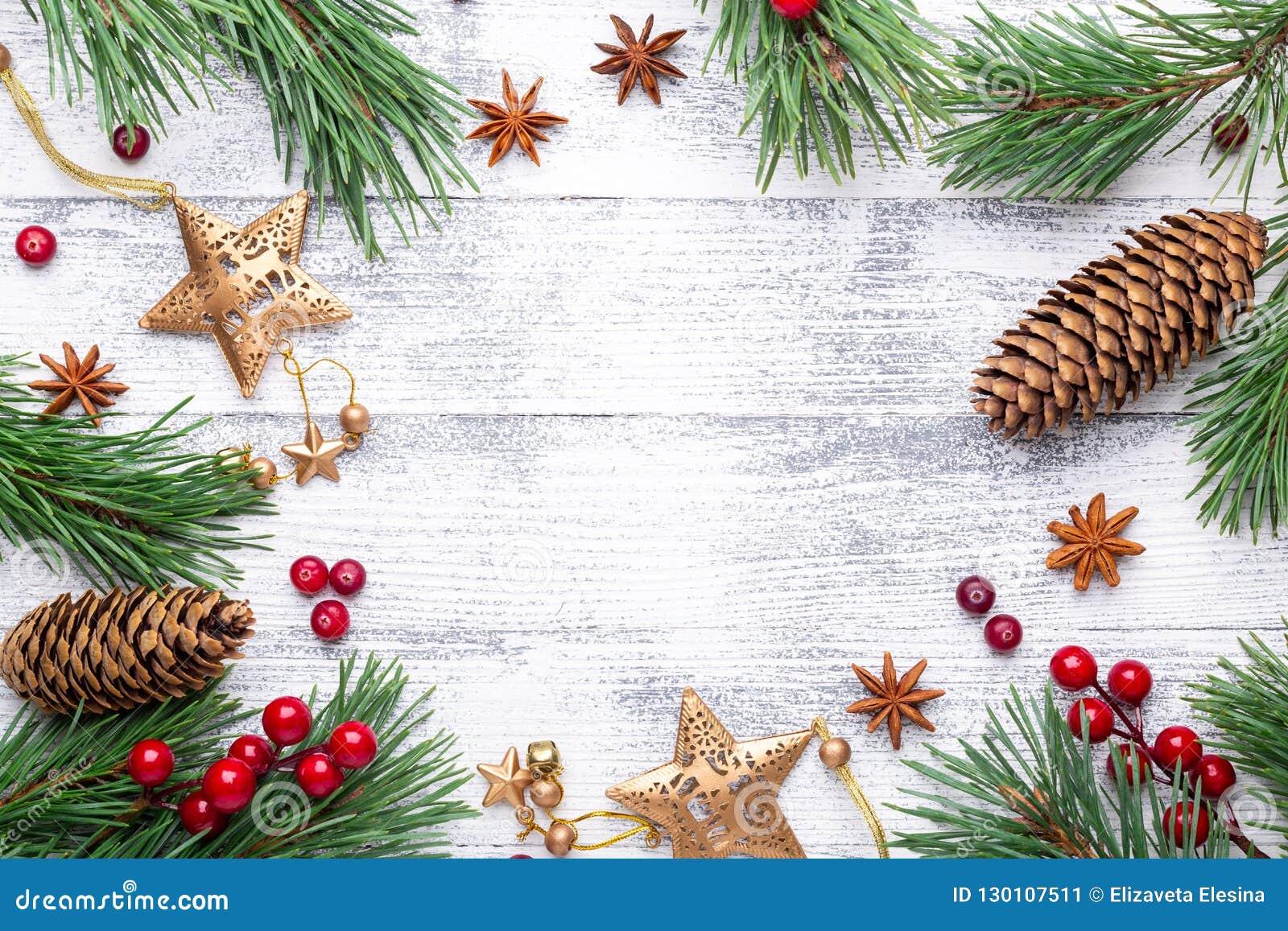 Fond de Noël Branches et cadeaux de sapin sur un fond en bois clair Canneberges, épices, baies de houx