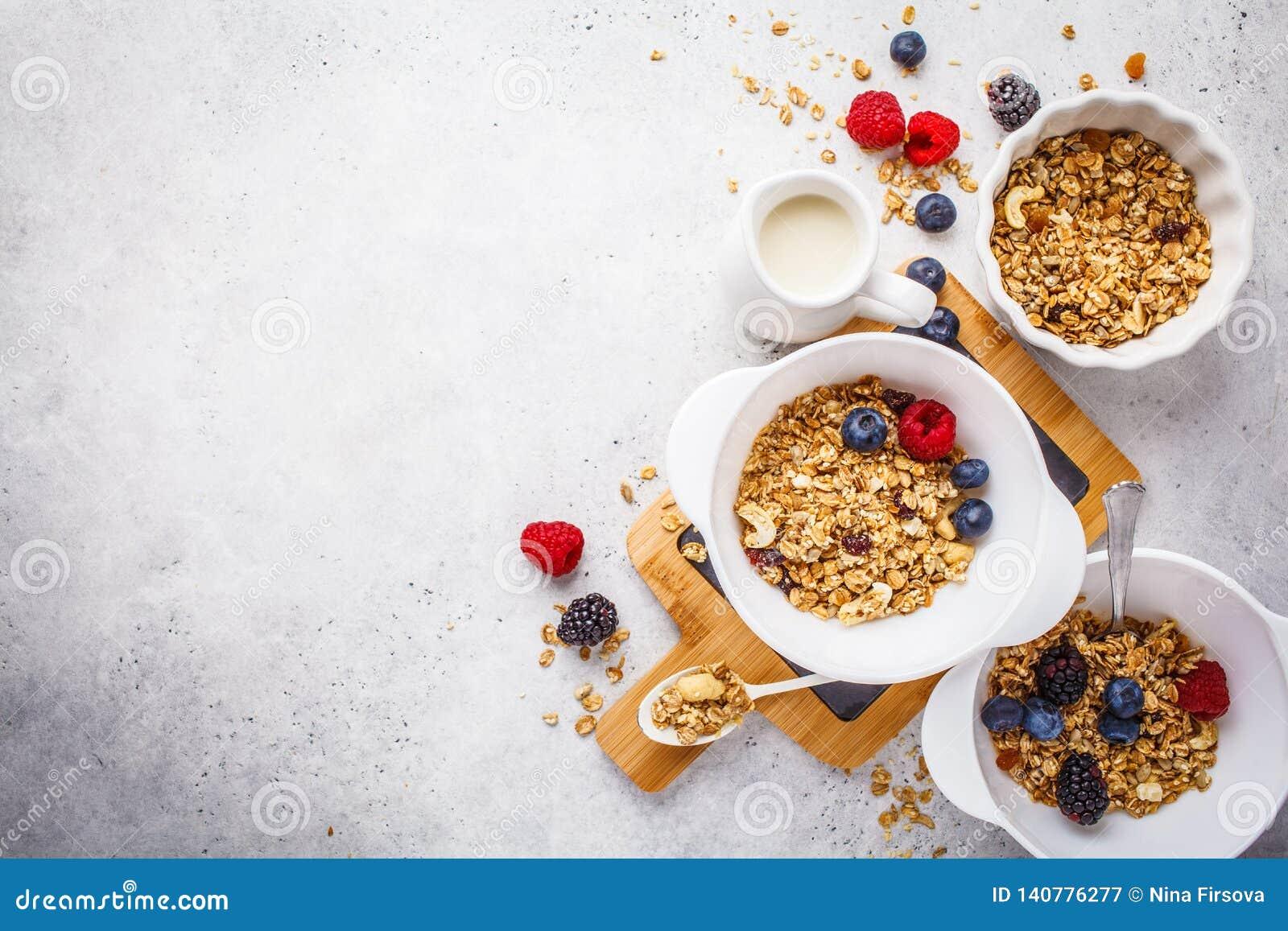 Fond de nourriture de petit déjeuner Granola avec du lait et des baies sur la table blanche