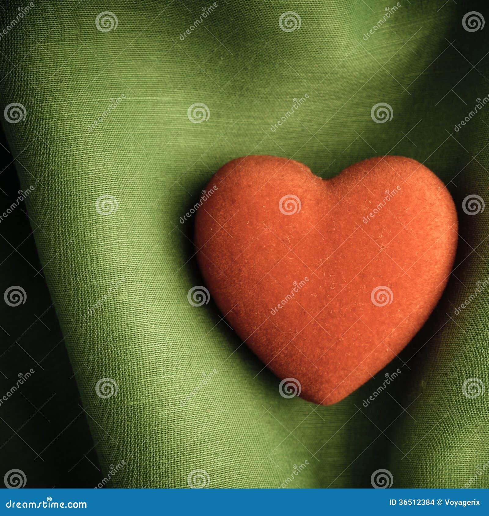 Fond de Saint-Valentin. Le coeur rouge sur le vert plie le tissu