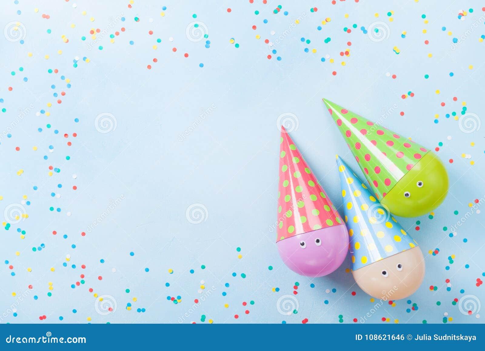 Fond drôle d anniversaire ou de partie Ballons et confettis colorés sur la vue supérieure bleue de table Configuration plate Cart