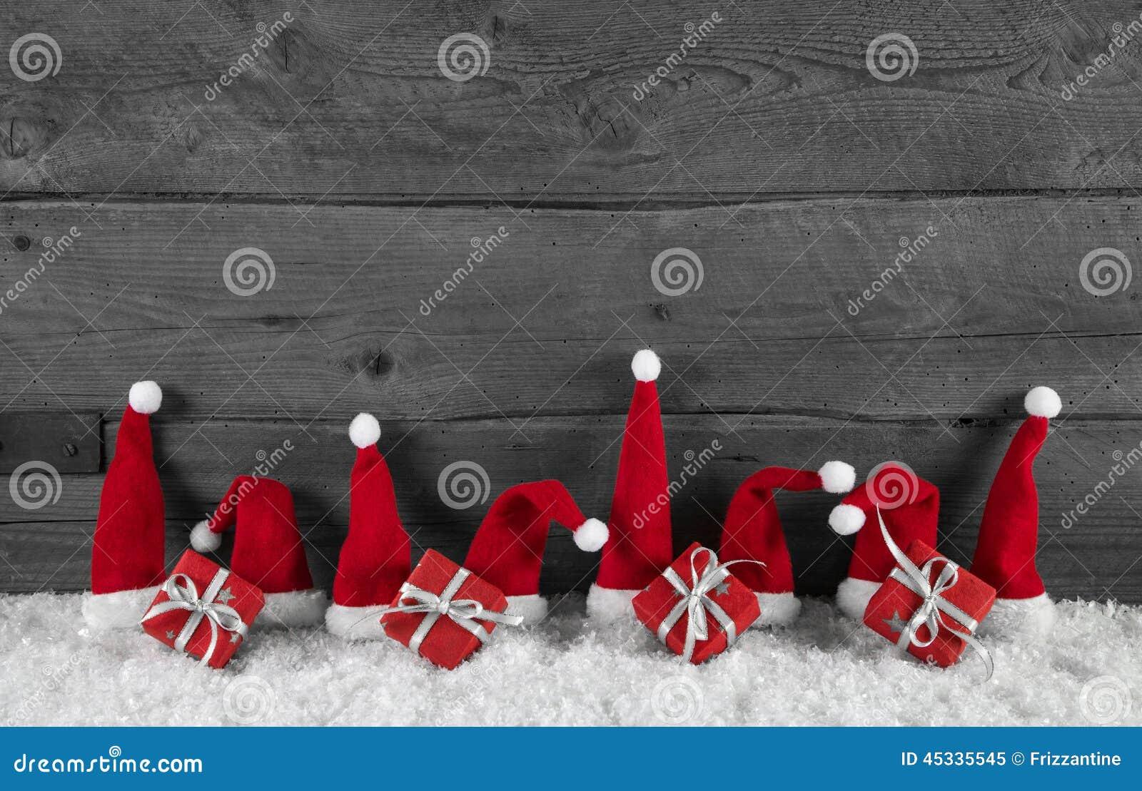 Fond gris en bois de Noël avec les chapeaux et les cadeaux rouges de Santa