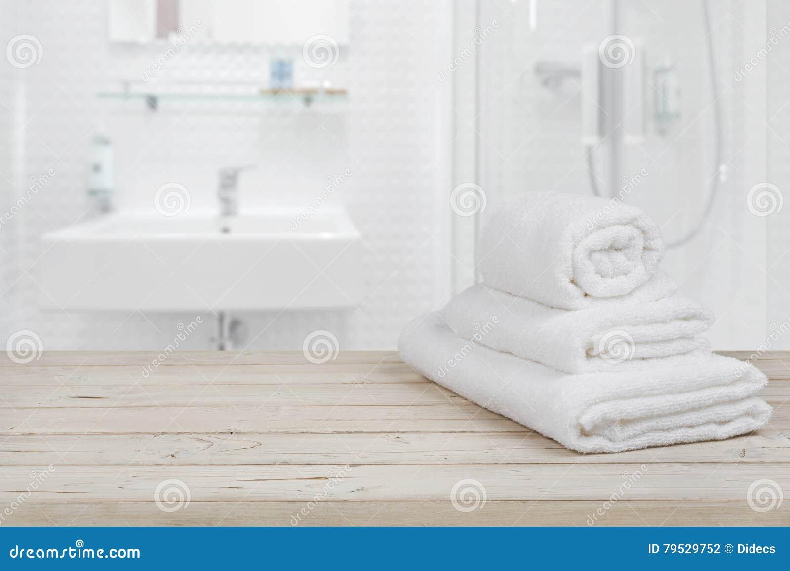 Fond intérieur brouillé de salle de bains et serviettes blanches de station thermale sur le bois