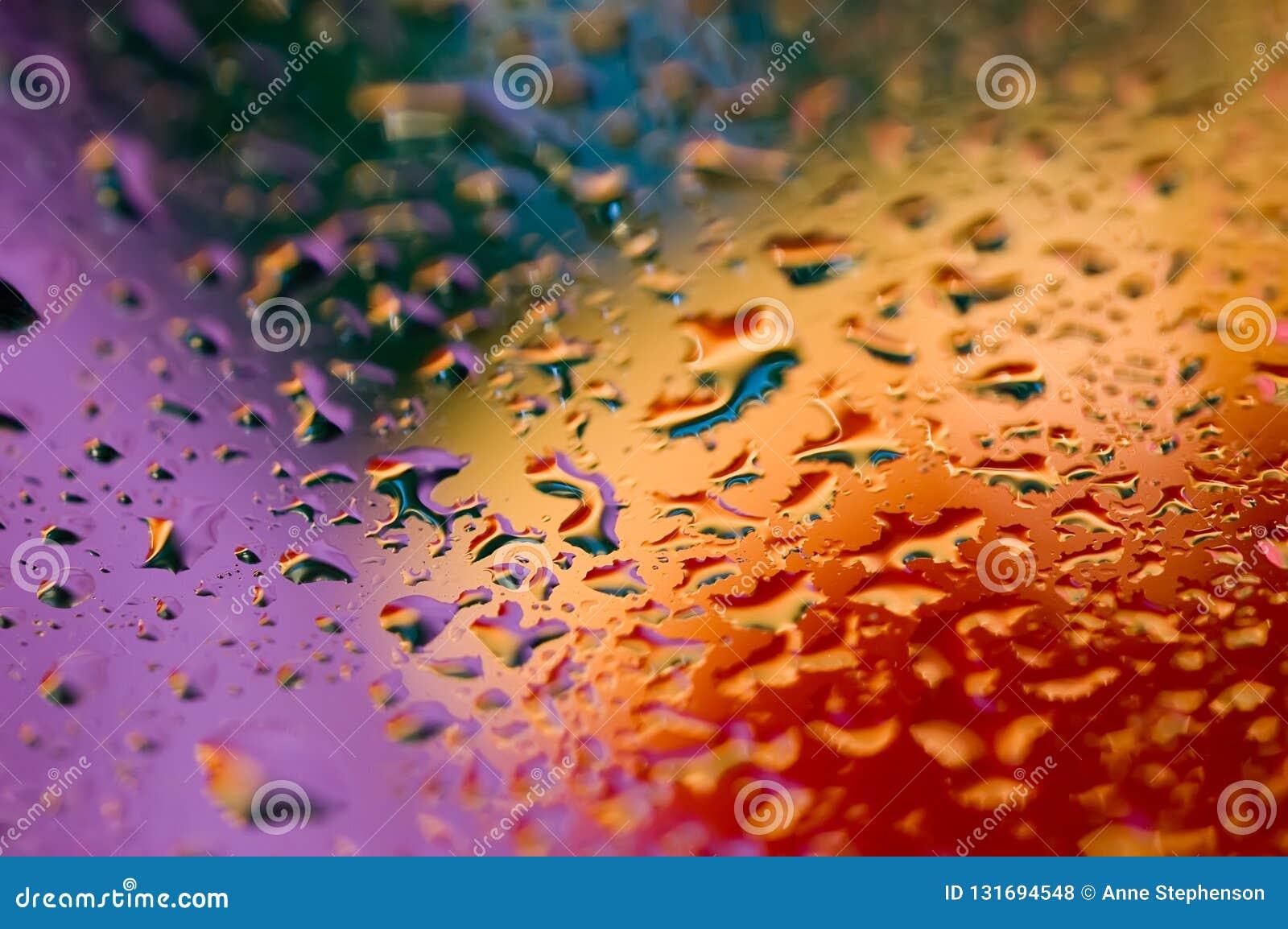 Fondo abstracto colorido de gotas púrpuras, azules, rojas y anaranjadas del agua